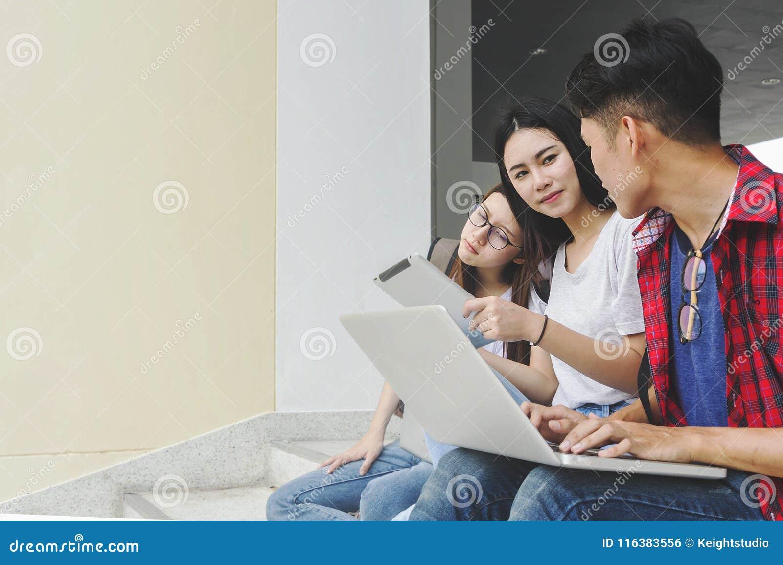 Ομάδα ελκυστικών νέων που χρησιμοποιούν ένα lap-top και μια ταμπλέτα, sitt