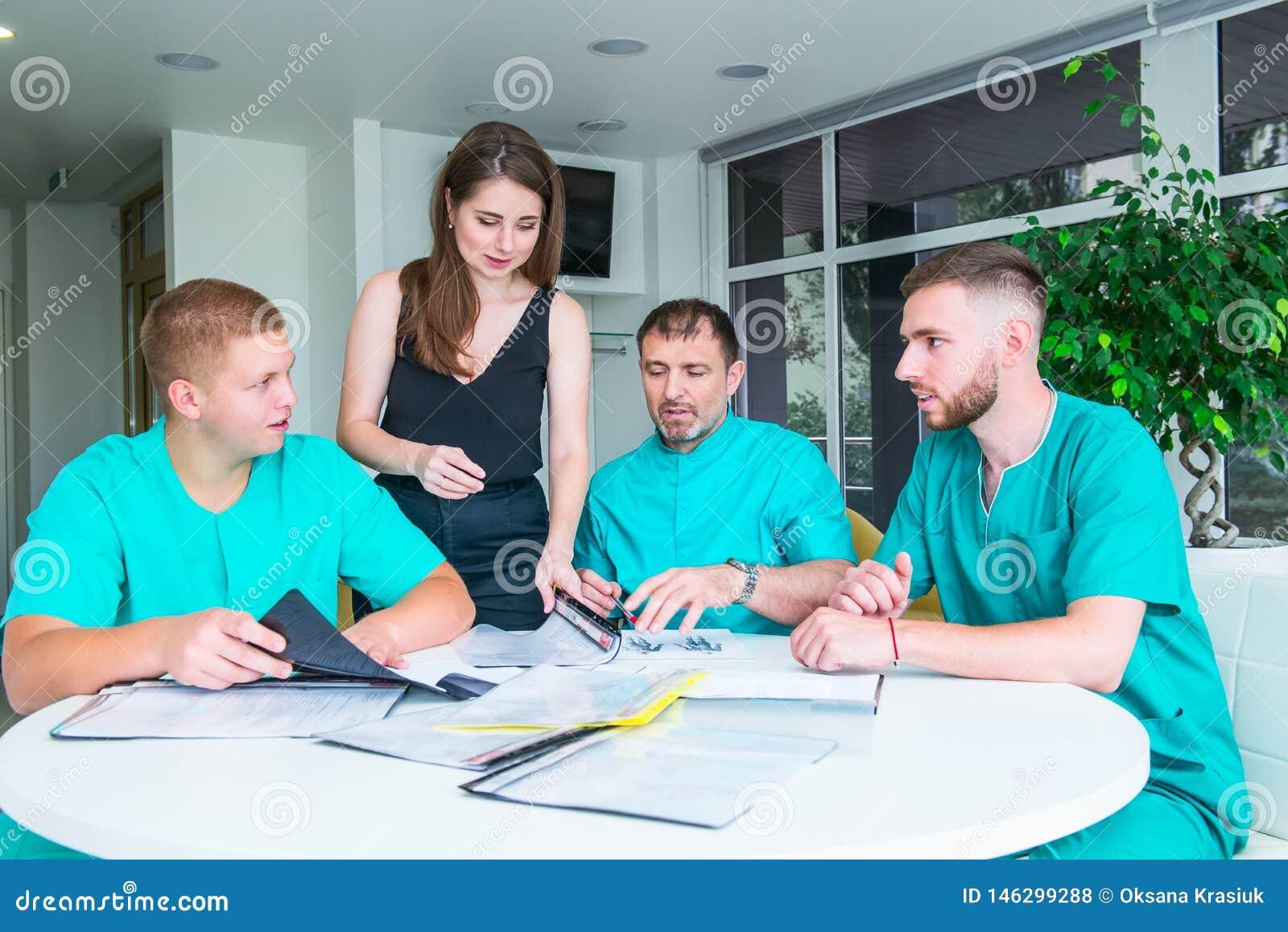Ομάδα ευτυχών γιατρών ή οικότροφων με τη συνεδρίαση και τη λήψη των συμβούλων των σημειώσεων στο νοσοκομείο ιατρική εκπαίδευση, υ