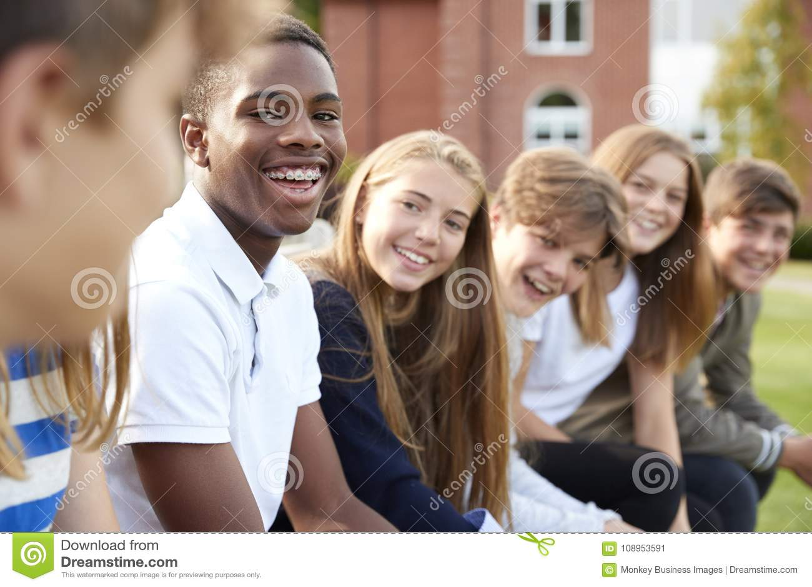 Ομάδα εφηβικών σπουδαστών που κάθονται έξω από τα σχολικά κτίρια