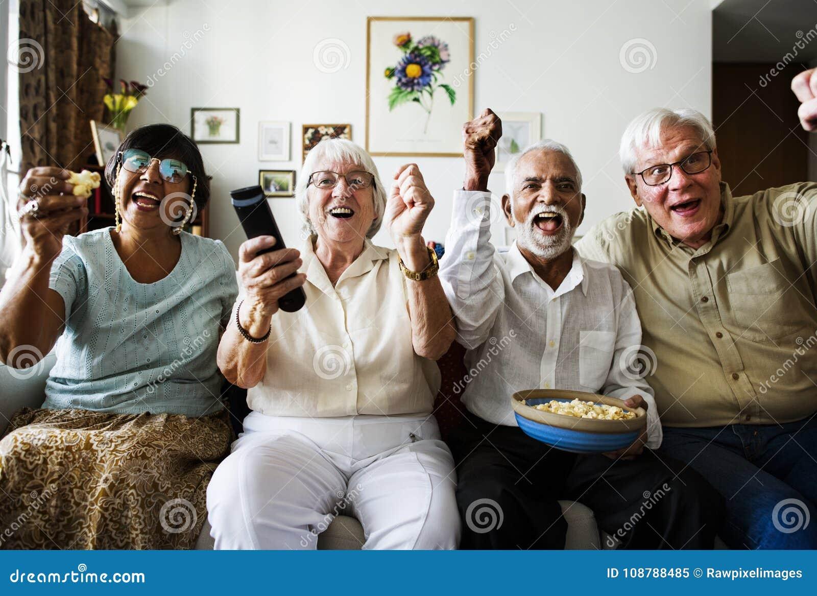 Ομάδα εύθυμων ανώτερων φίλων που κάθονται και που προσέχουν τη TV από κοινού