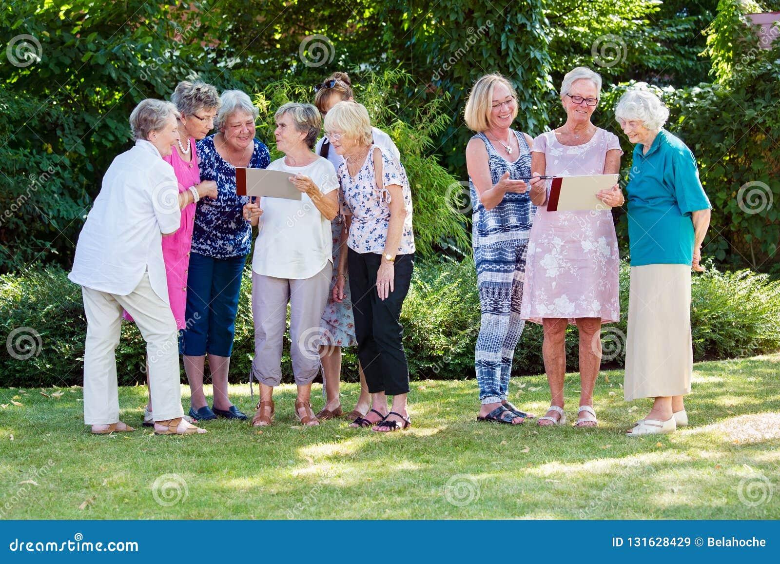 Ομάδα ηλικιωμένων κυριών σε ένα σπίτι προσοχής που απολαμβάνει μια παρακινητική δημιουργική κατηγορία τέχνης υπαίθρια σε έναν κήπ