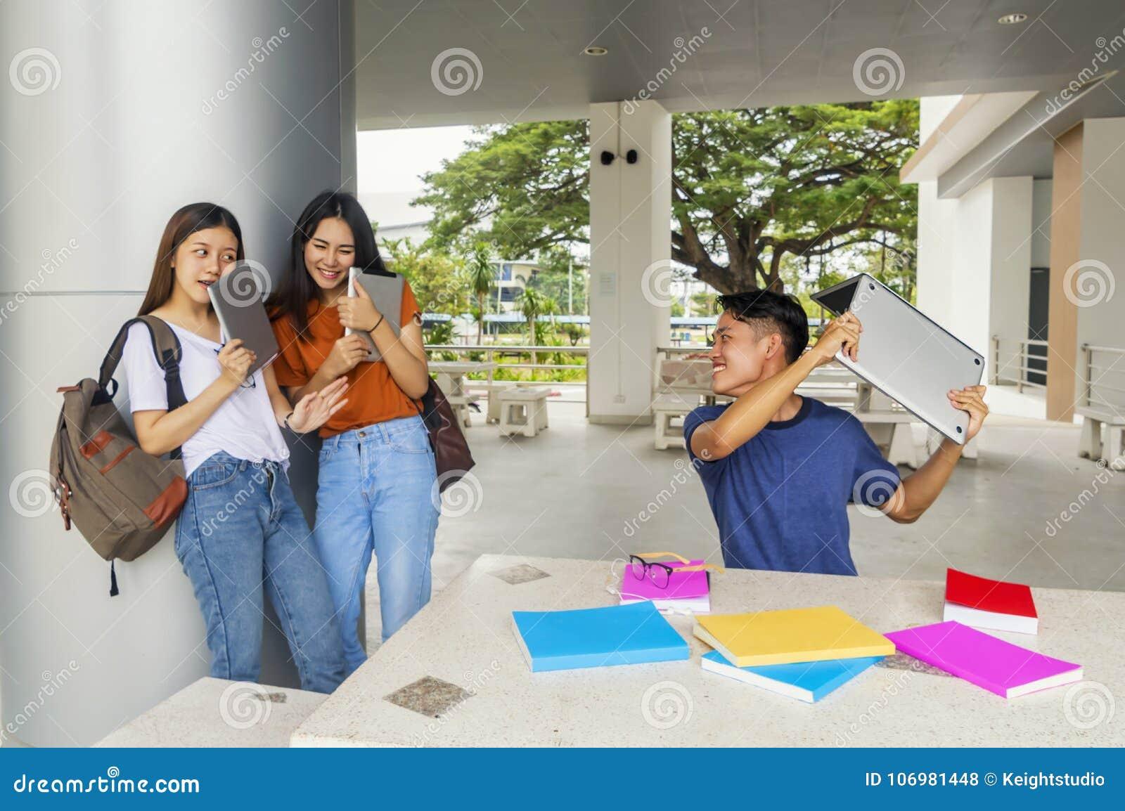 Ομάδα νέου Ασιάτη που μελετά στον πανεπιστημιακό παίζοντας συνταγματάρχη σπουδαστών