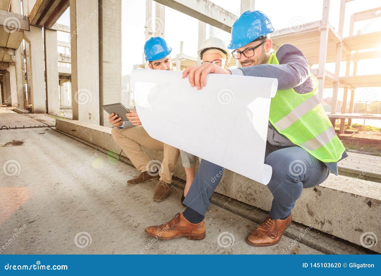 Ομάδα νέων αρχιτεκτόνων που εξετάζουν τα σχέδια ορόφων κατά τη διάρκε