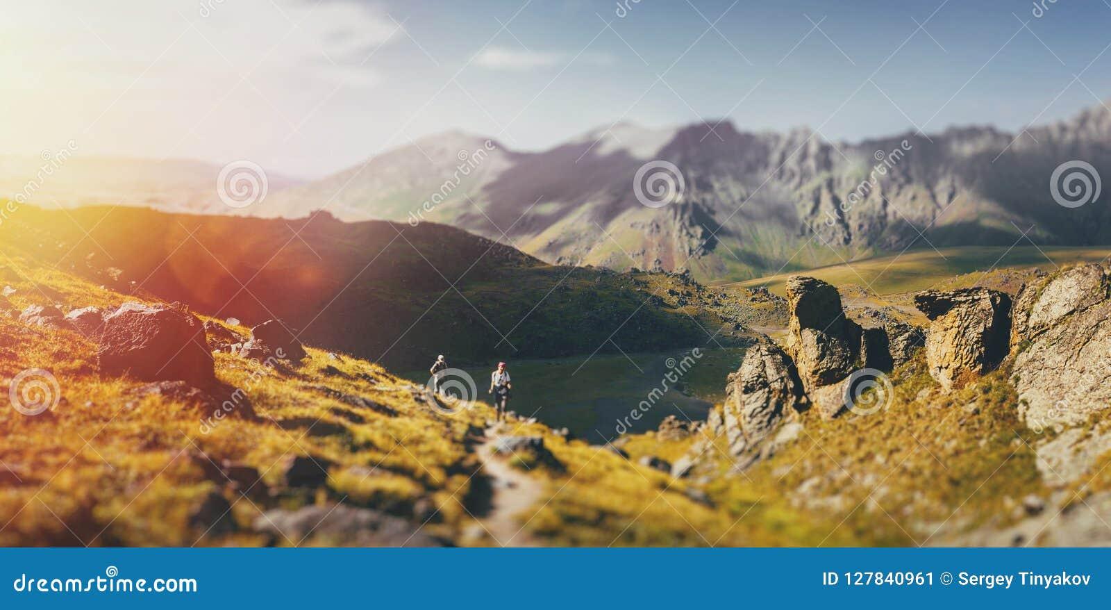 Ομάδα οδοιπόρων που περπατούν εμπρός στα θερινά βουνά, έννοια ταξιδιού ταξιδιών