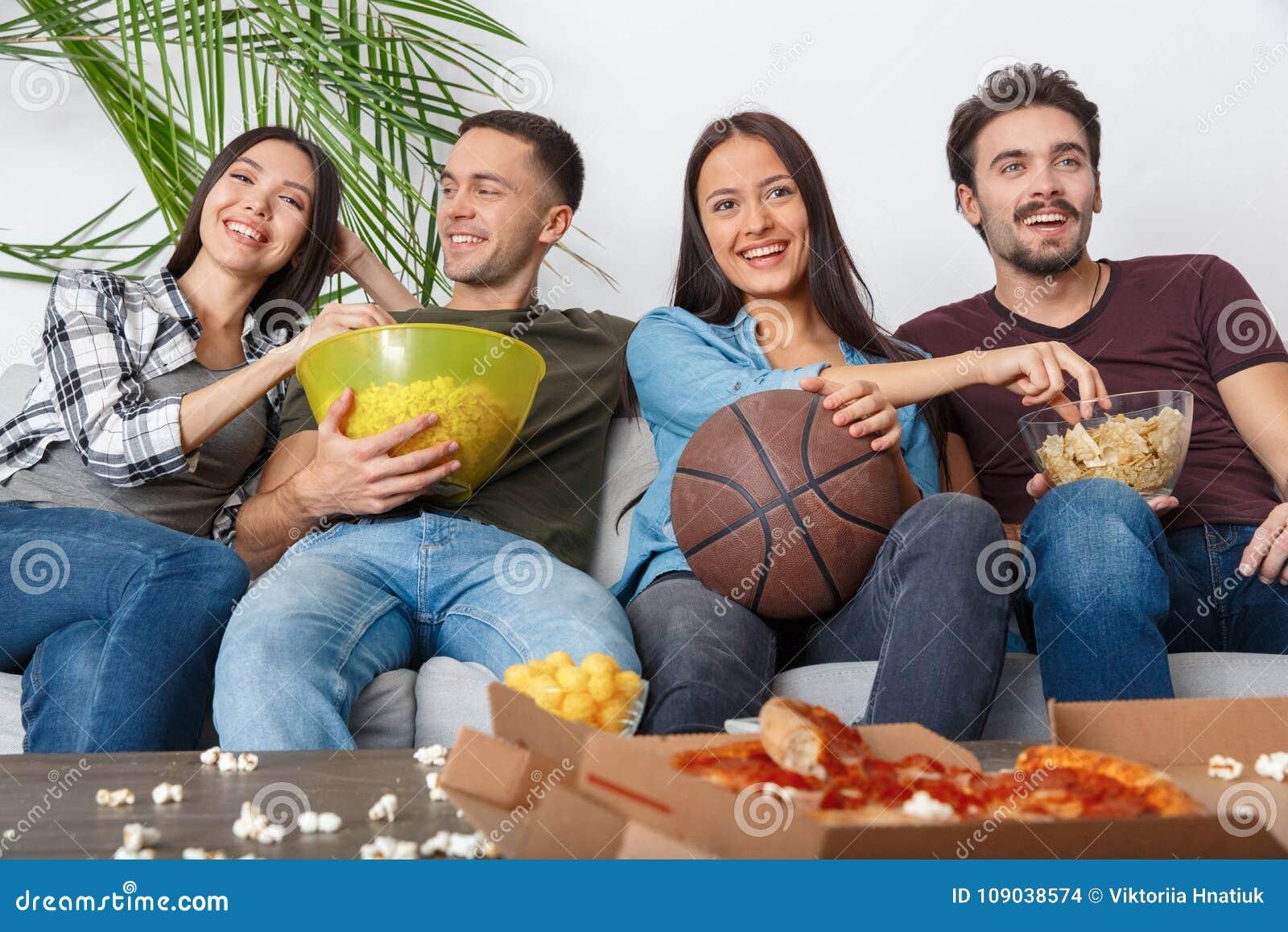Ομάδα οπαδών αθλήματος φίλων που προσέχει το παιχνίδι καλαθοσφαίρισης τα πρόχειρα φαγητά