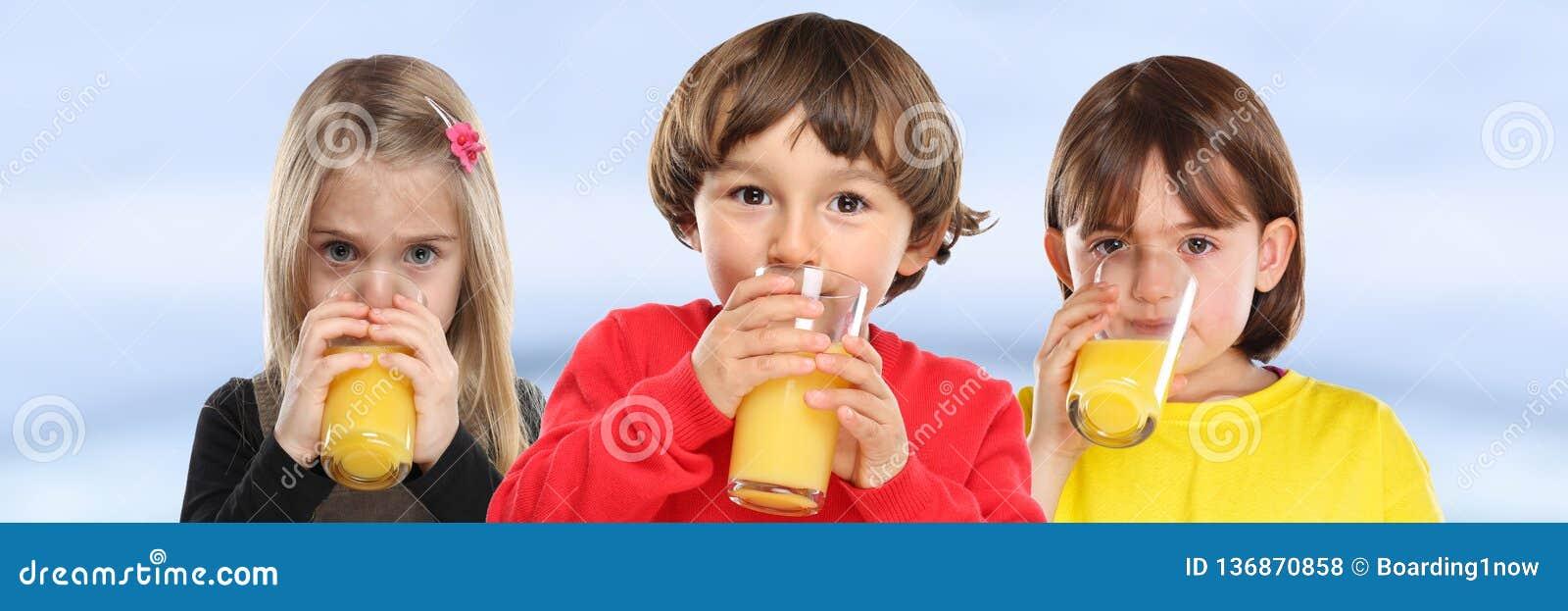 Ομάδα παιδιών αγοριών κοριτσιών παιδιών που πίνουν το υγιές έμβλημα κατανάλωσης χυμού από πορτοκάλι