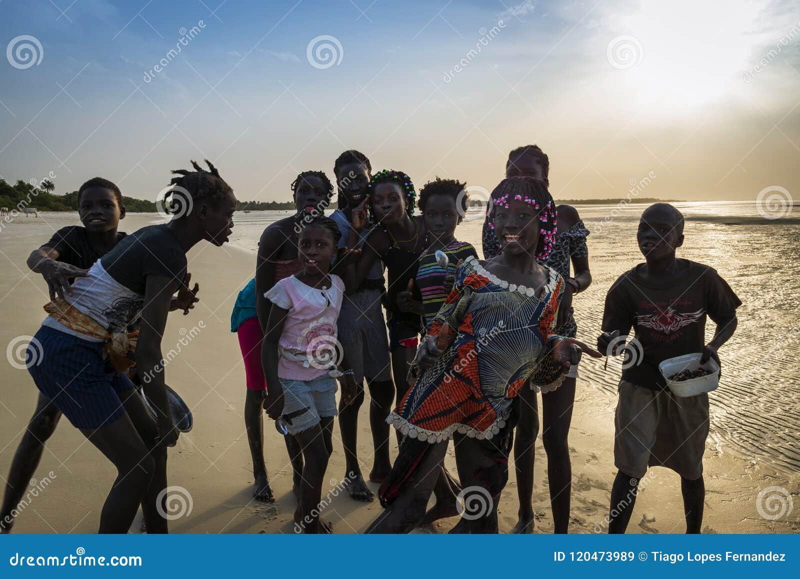 Ομάδα παιδιών που παίζουν από την παραλία στο νησί Orango στο ηλιοβασίλεμα, στη Γουινέα-Μπισσάου