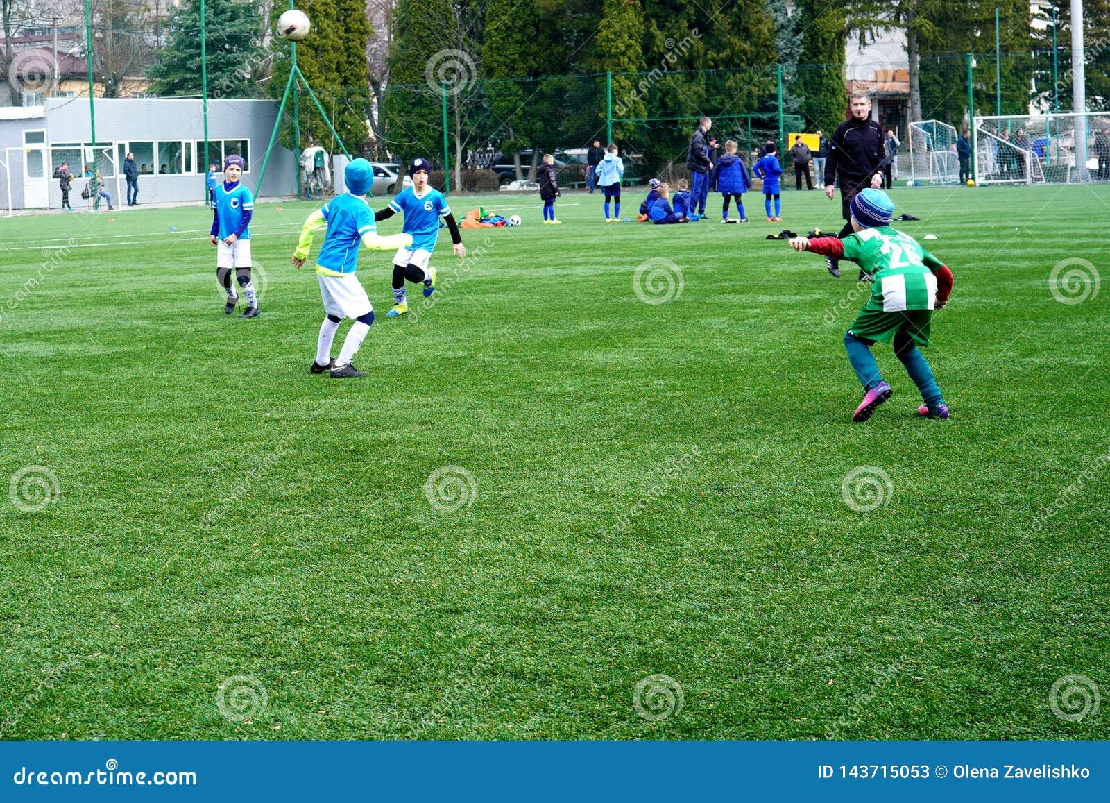 Ομάδα ποδοσφαίρου παιδιών στην πίσσα Έδαφος κατάρτισης ποδοσφαίρου παιδιών Νέοι ποδοσφαιριστές που τρέχουν μετά από τη σφαίρα