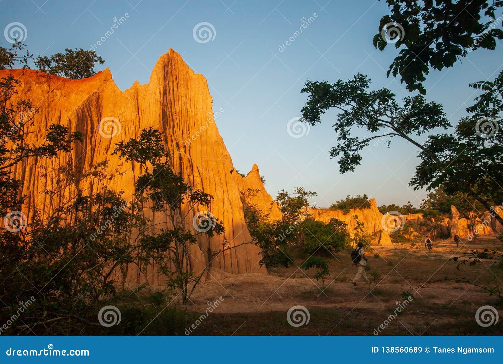 Ομάδα τουριστών στο αρχαίο φυσικό τοπίο στο ηλιοβασίλεμα Η περιοχή NA Noi Σάο DIN επιδεικνύει το γραφικό τοπίο του διαβρωμένου ψα