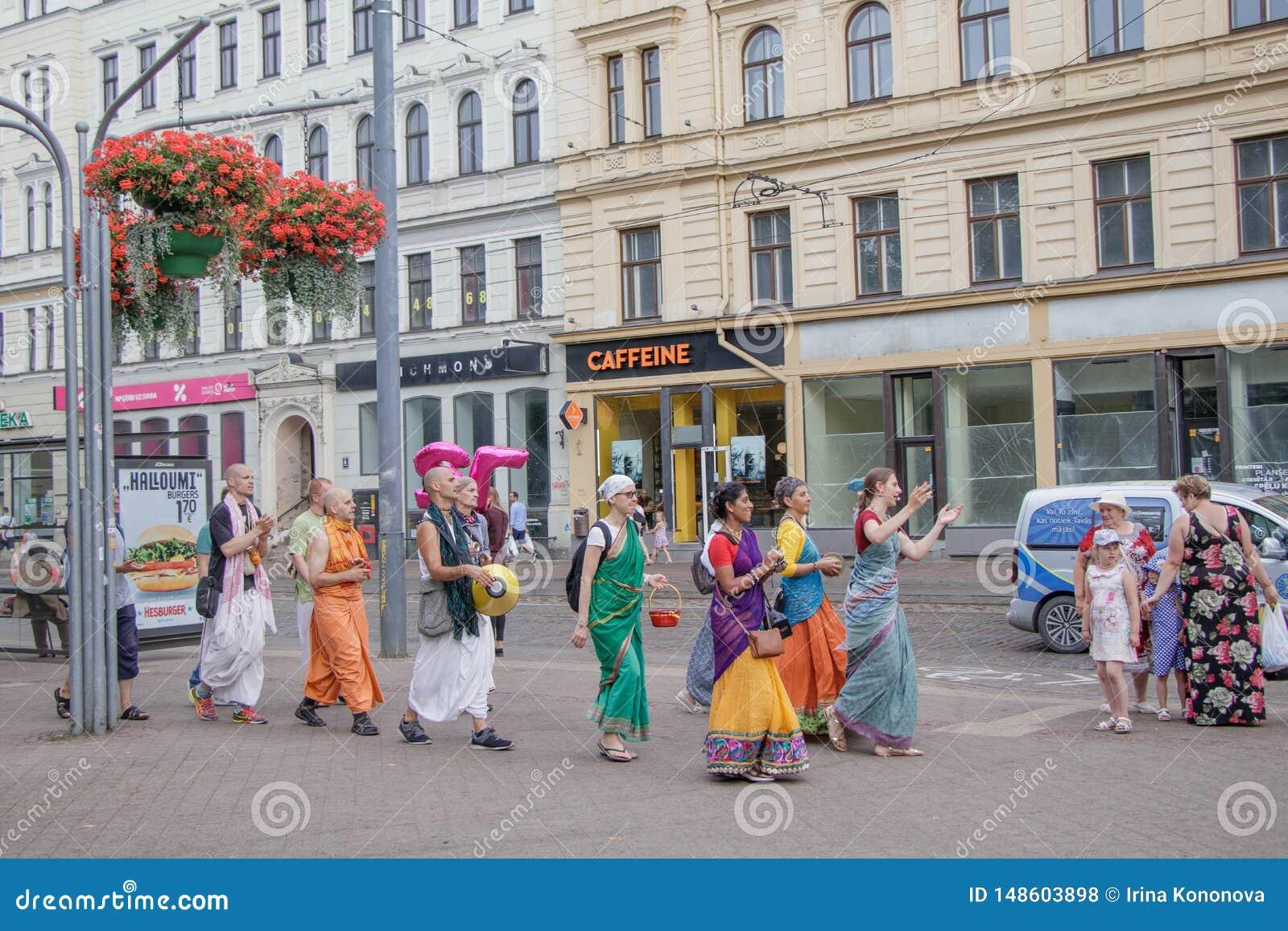 Ομάδα των ανθρώπων Krishna λαγών που περπατούν και που τραγουδούν στις οδούς της Ρήγας