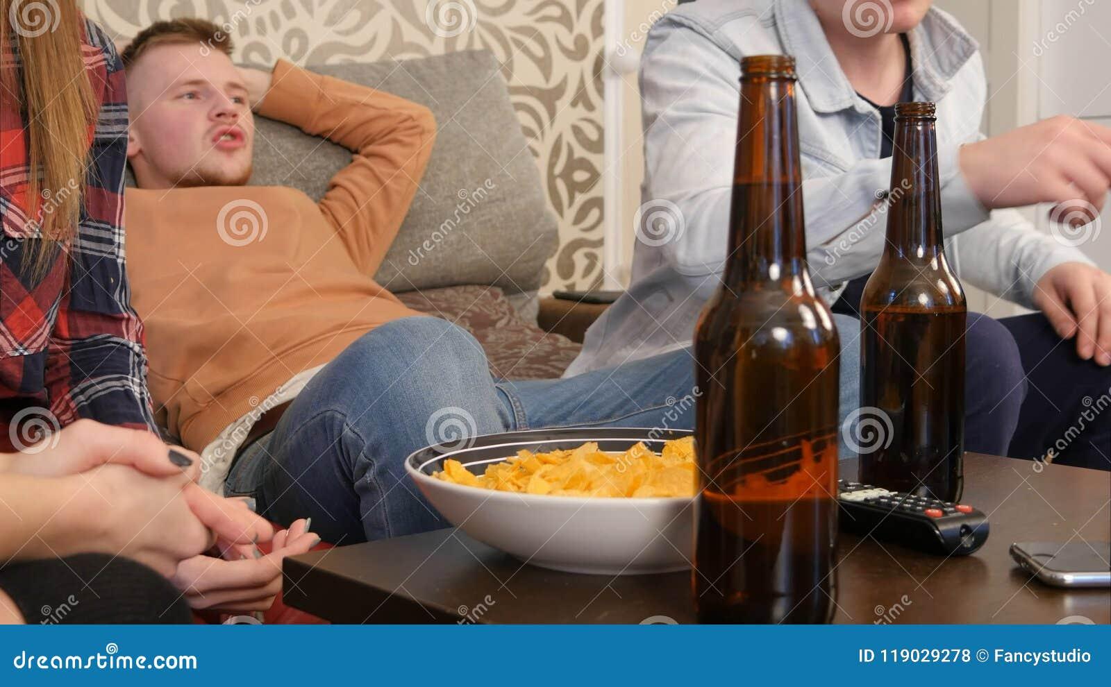 Ομάδα φίλων που κάθονται στον καναπέ, τη TV προσοχής μαζί και την μπύρα κατανάλωσης