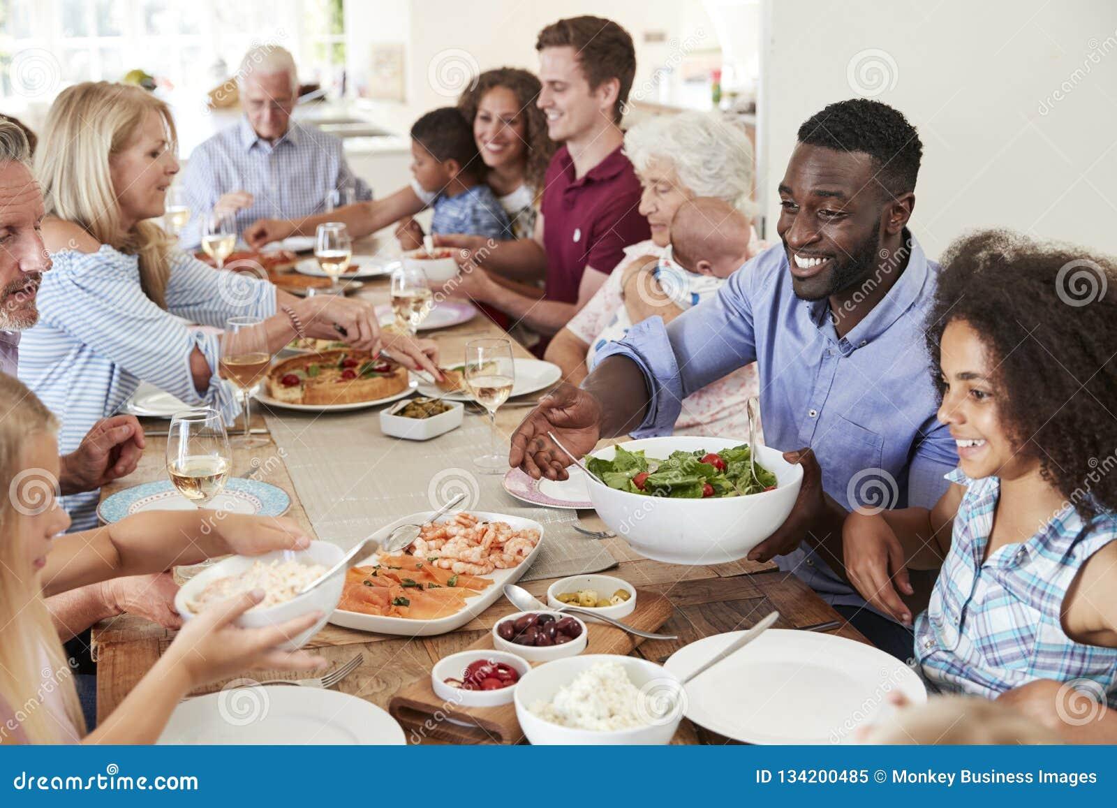 Ομάδα Multi-Generation οικογένειας και φίλων που κάθονται τον πίνακα και που απολαμβάνουν το γεύμα