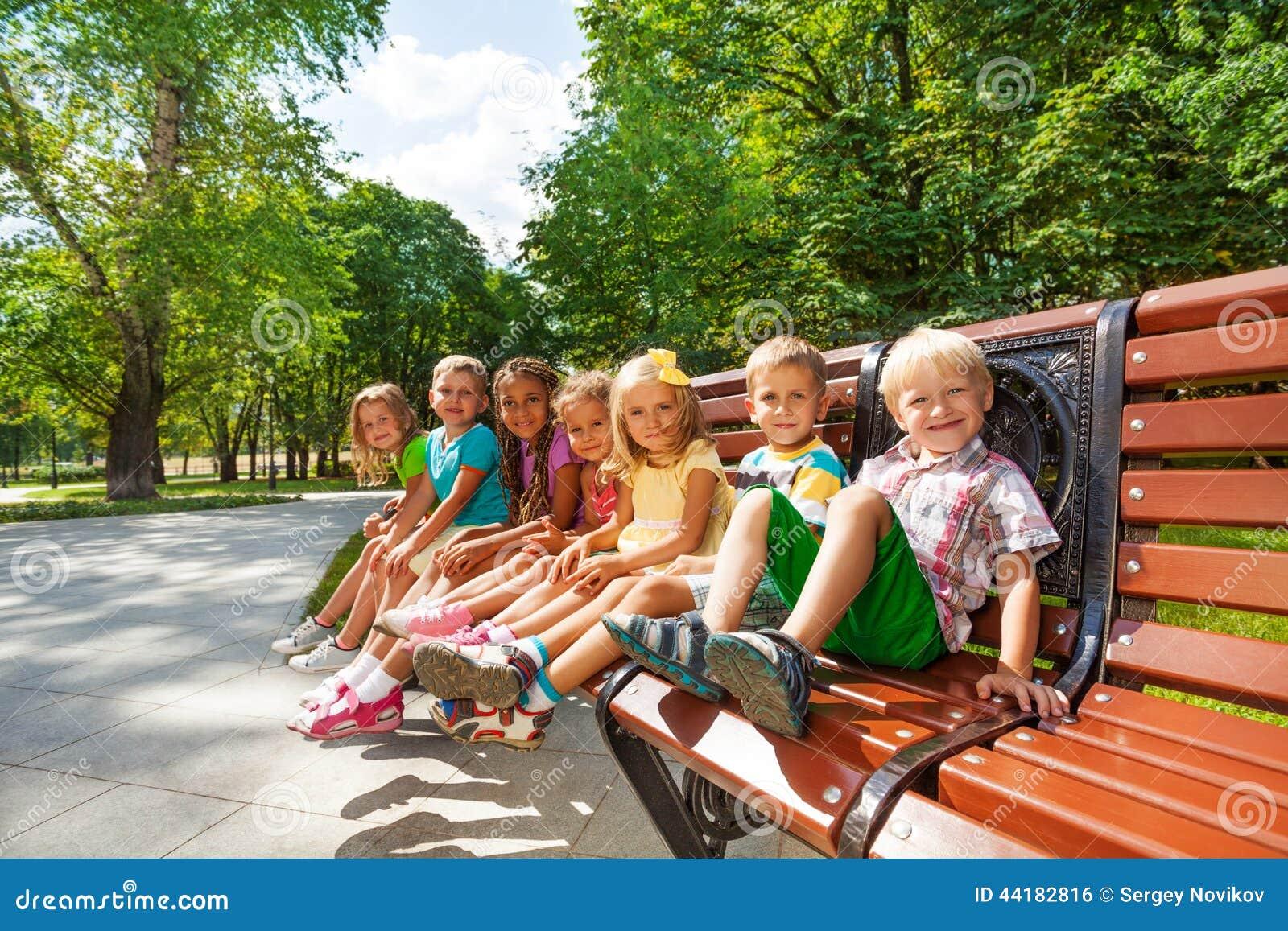 Ομάδα ή υπόλοιπο παιδιών στον πάγκο στο πάρκο