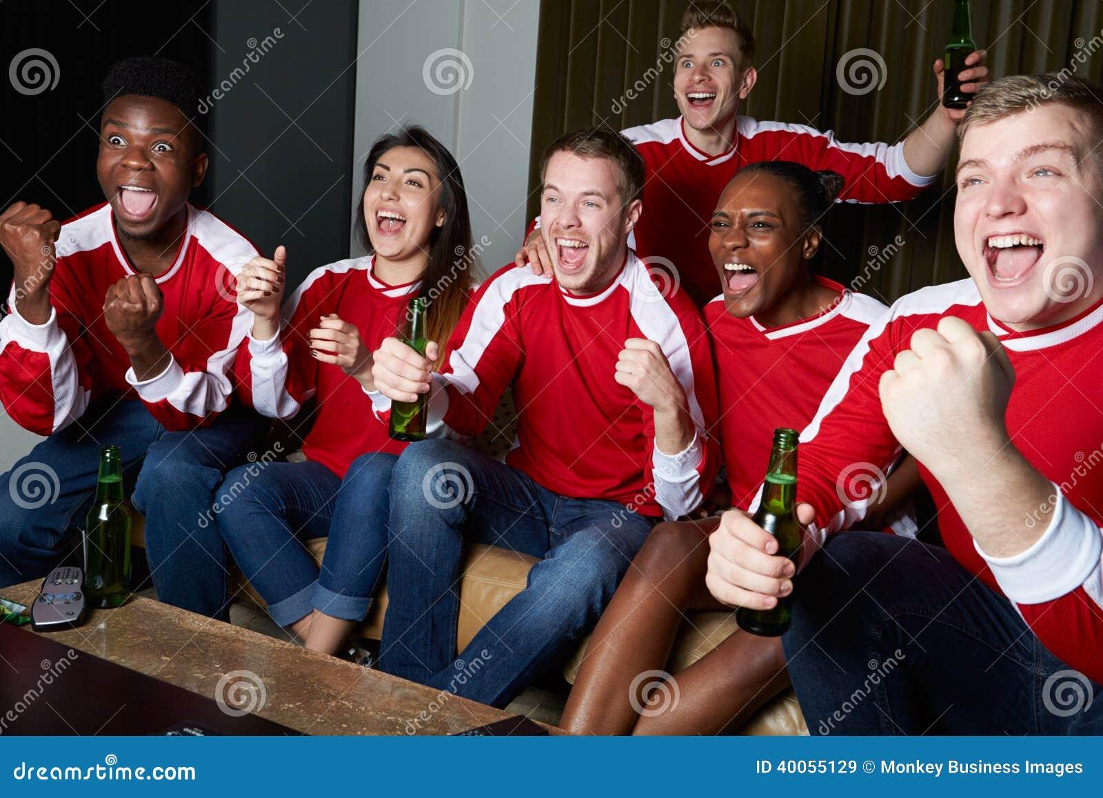 Ομάδα αθλητικών ανεμιστήρων που προσέχει το παιχνίδι στη TV στο σπίτι