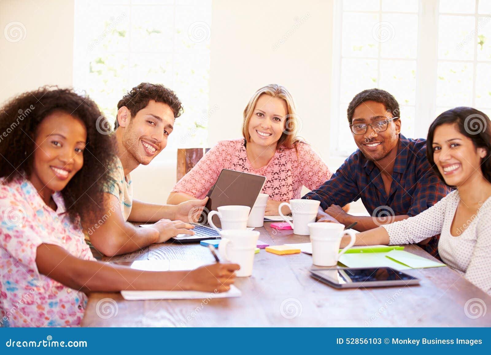Ομάδα επιχειρηματιών που κάθονται τον πίνακα στη συνεδρίαση