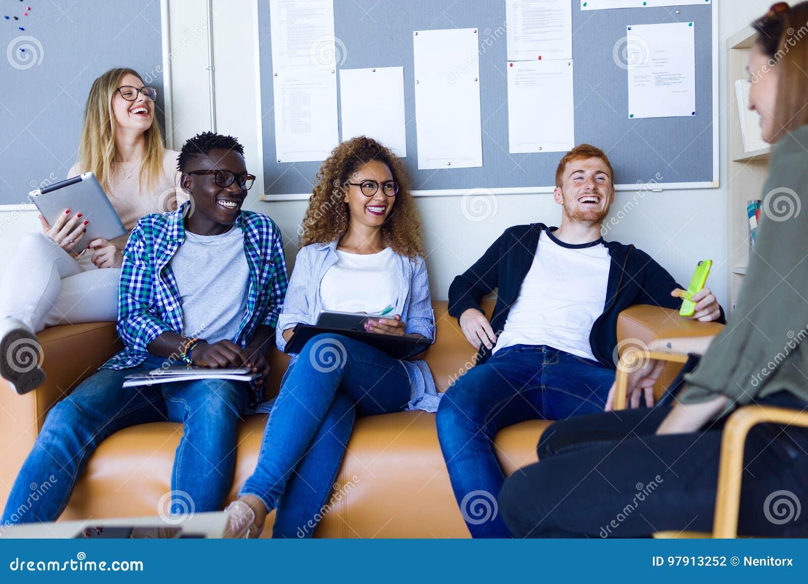 Ομάδα ευτυχών νέων σπουδαστών που μιλούν σε ένα πανεπιστήμιο