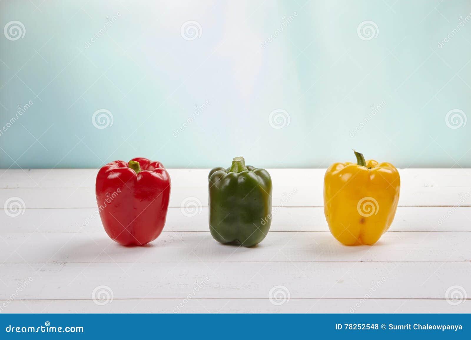 Ομάδα ζωηρόχρωμων πιπεριών στο ξύλινο υπόβαθρο