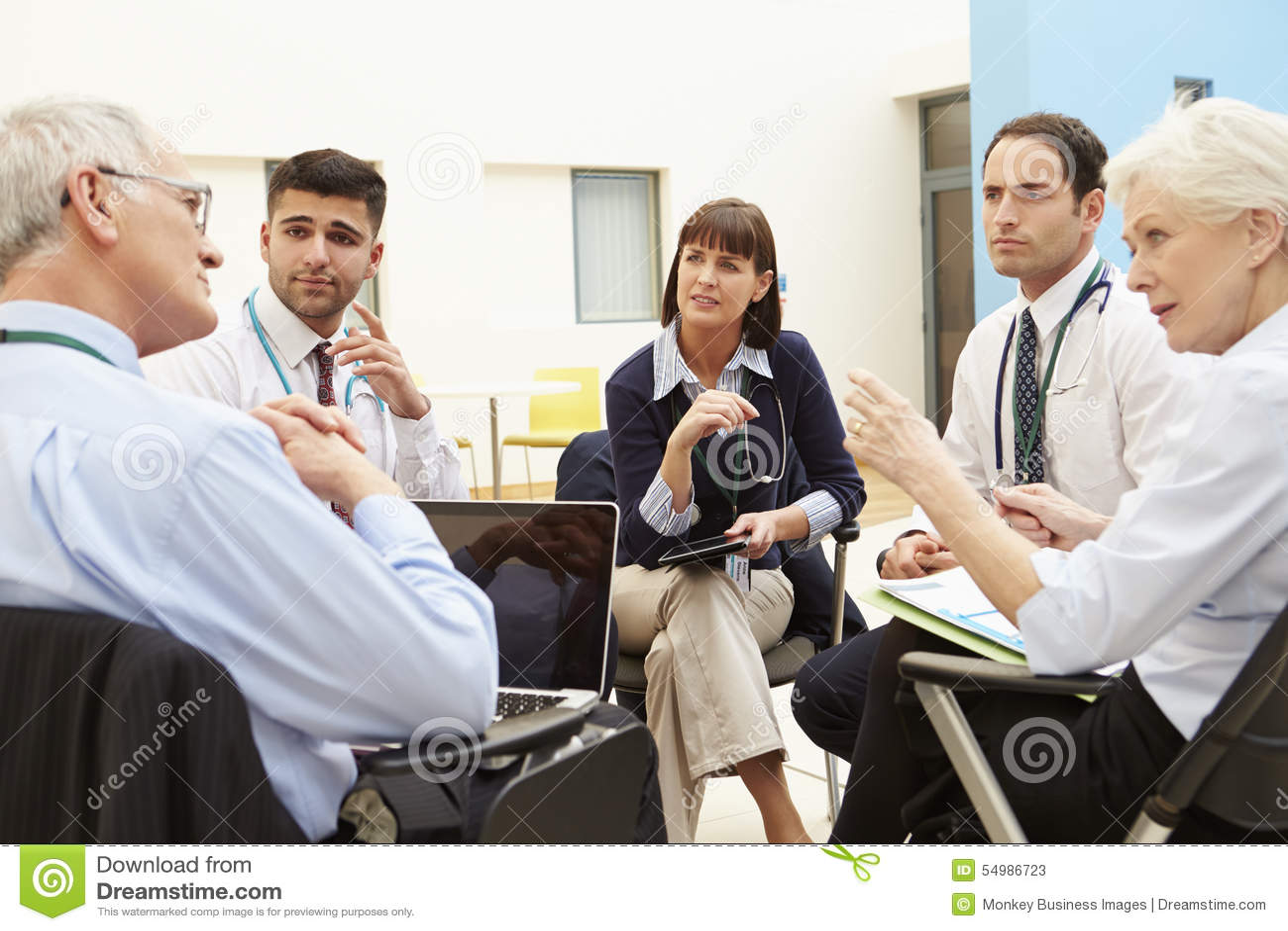 Ομάδα συμβούλων που κάθονται στον πίνακα στη συνεδρίαση των νοσοκομείων
