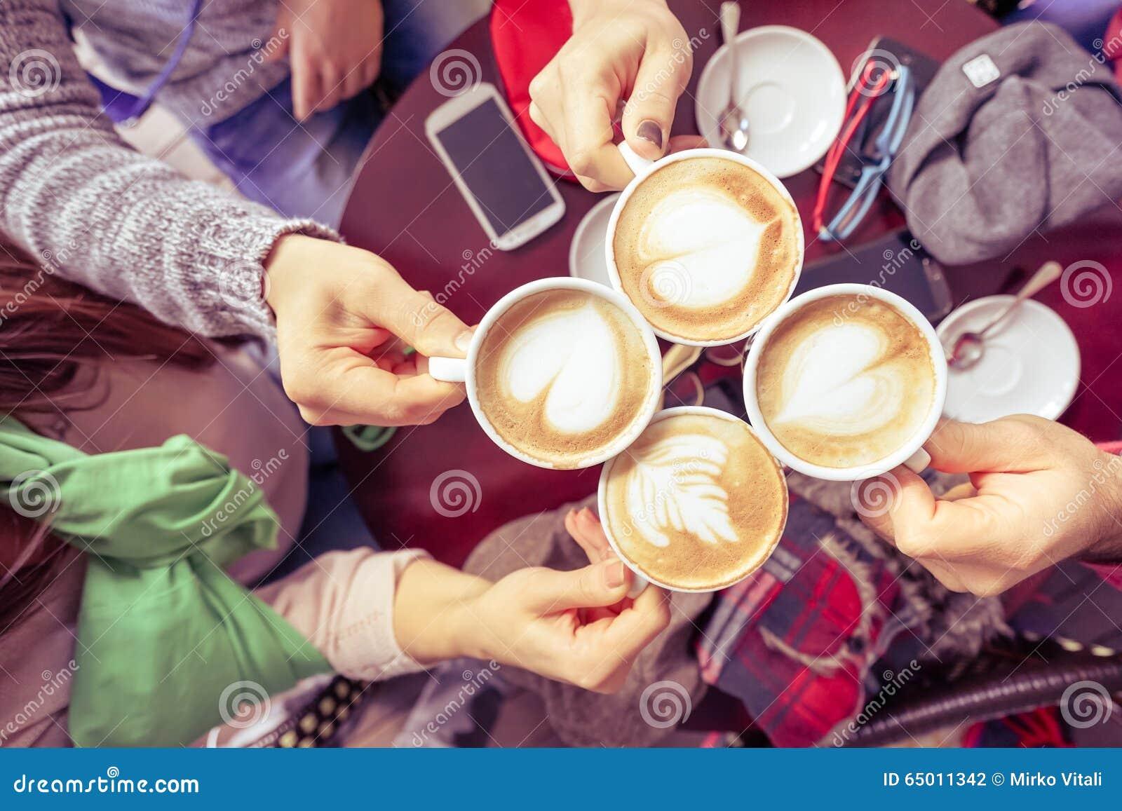 Ομάδα φίλων που πίνουν το cappuccino στο εστιατόριο φραγμών καφέ