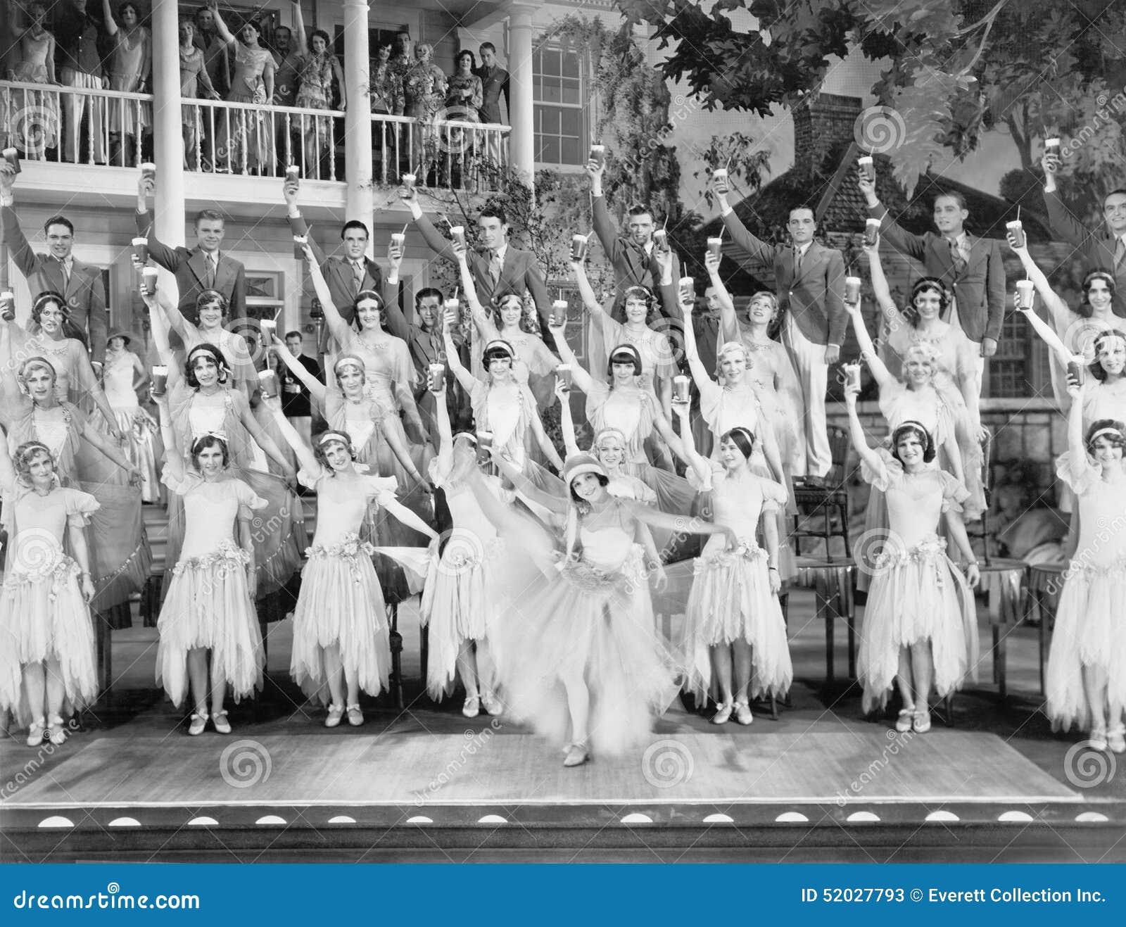 Ομάδα χορευτών που στέκονται σε ένα στάδιο με τα όπλα τους στον αέρα και ένα ποτό στα χέρια τους (όλα τα πρόσωπα που απεικονίζοντ