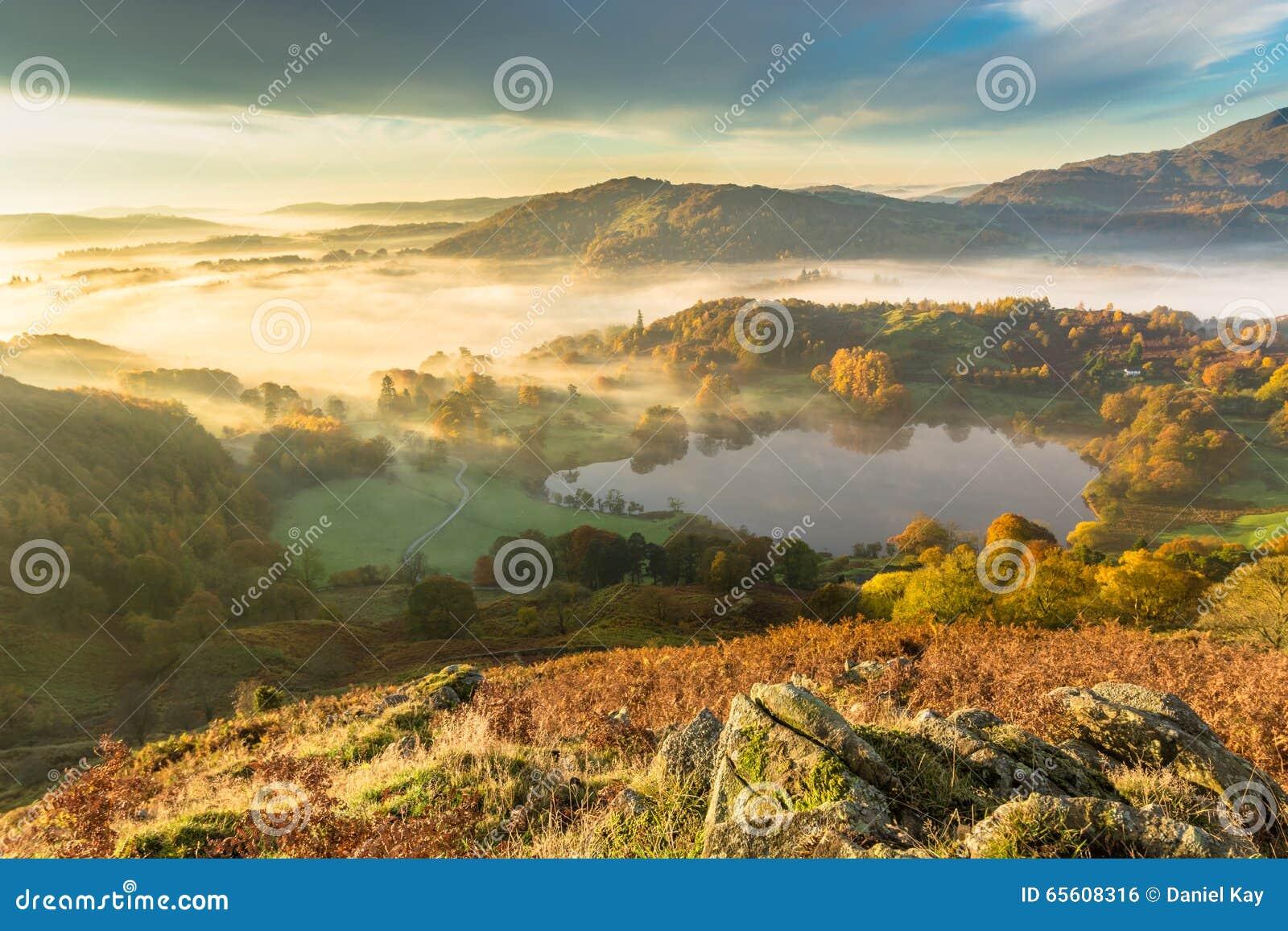 Ομίχλη φθινοπώρου που καθυστερεί πέρα από Loughrigg Tarn στην αγγλική περιοχή λιμνών