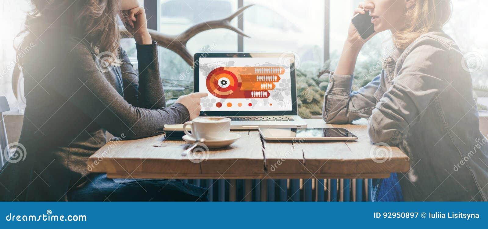 Ομαδική εργασία, δύο νέες επιχειρηματίες που κάθεται πέρα από τον πίνακα μεταξύ τους Στο επιτραπέζιο lap-top, φλυτζάνι καφέ και υ