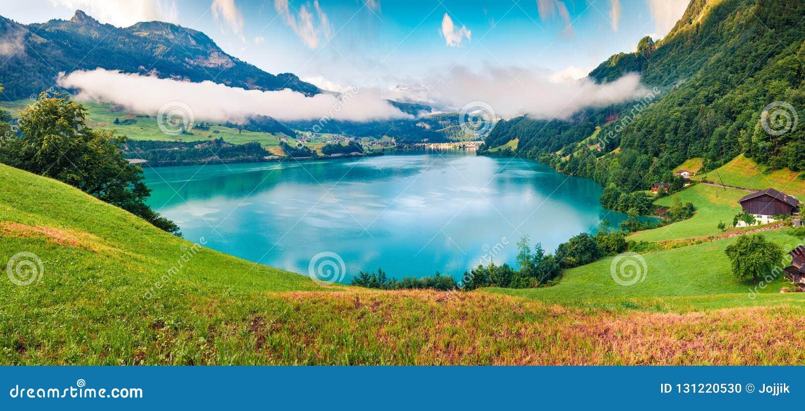 Ομιχλώδες θερινό πανόραμα της λίμνης Lungerersee Ζωηρόχρωμη άποψη πρωινού των ελβετικών Άλπεων, του χωριού θέση Lungern, Ελβετία,