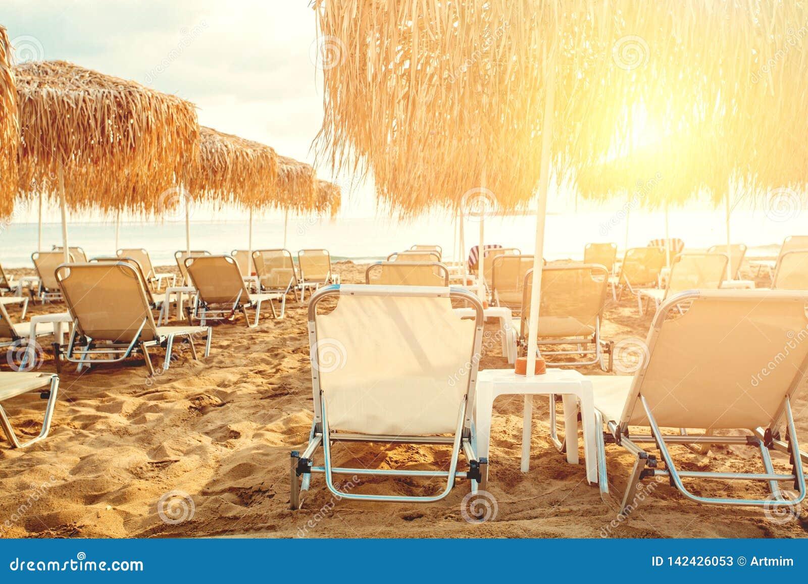 Ομπρέλες και sunbeds στο υπόβαθρο γραμμών παραλιών Διακοπές στην ωκεάνια παραλία, έννοια καλοκαιρινών διακοπών