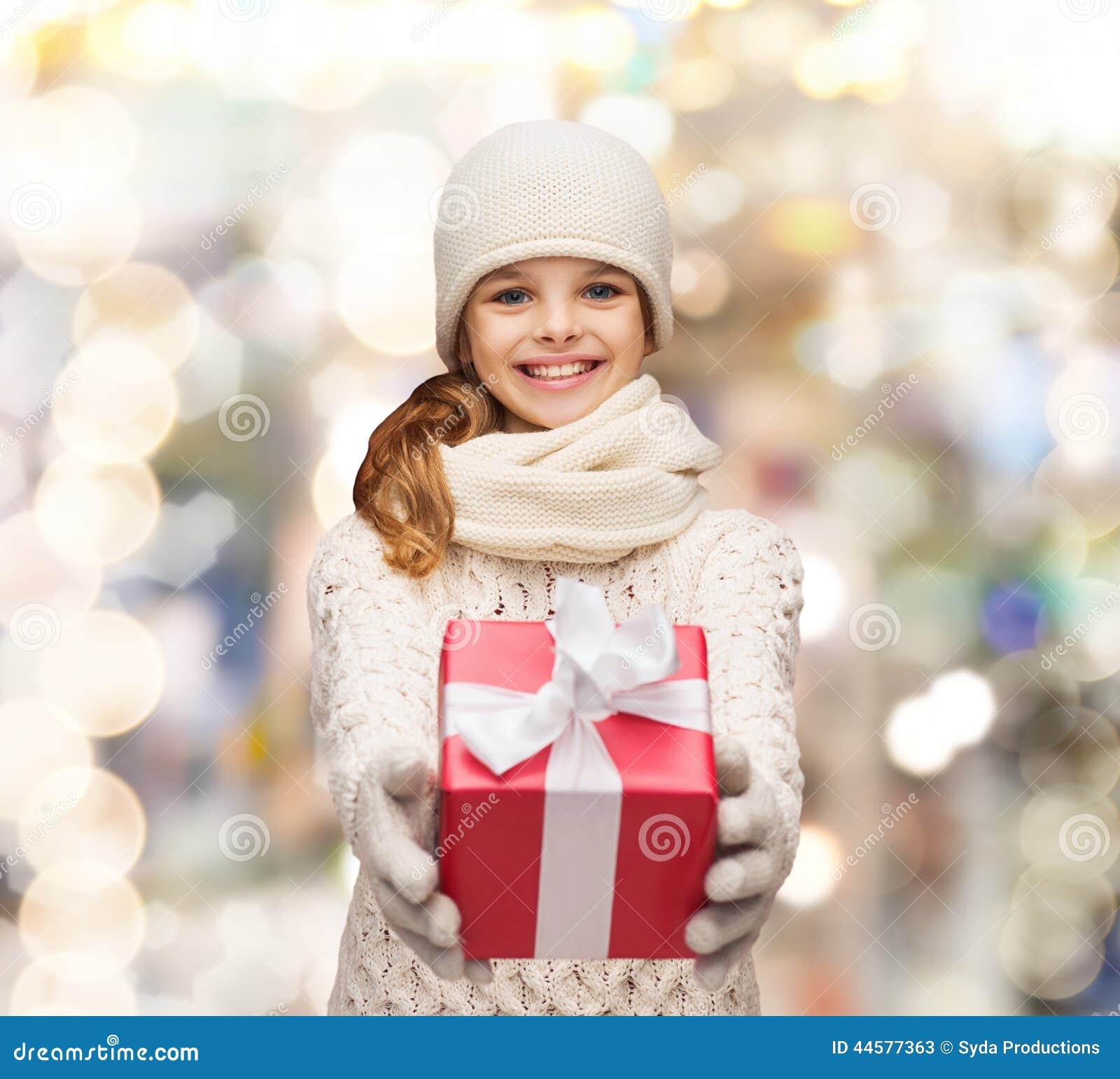 Ονειρεμένος κορίτσι στα χειμερινά ενδύματα με το κιβώτιο δώρων
