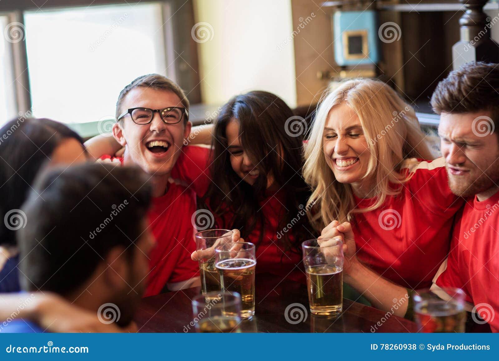 Οπαδοί ποδοσφαίρου ή φίλοι με την μπύρα στον αθλητικό φραγμό