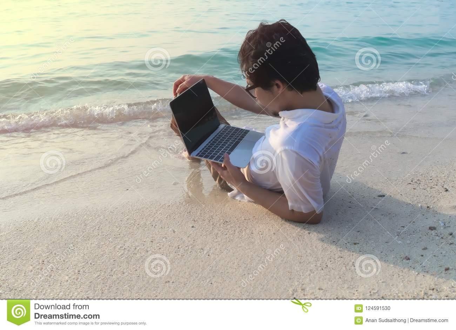 Οπισθοσκόπος του νέου ασιατικού ατόμου με το lap-top που ξαπλώνει στον αμμώδη της παραλίας