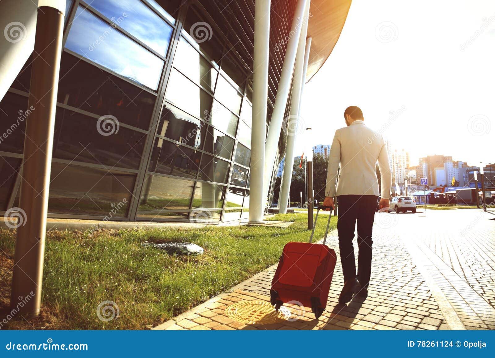 Οπισθοσκόπος του νέου περπατήματος επιχειρηματιών κάτω από την οδό με τις αποσκευές