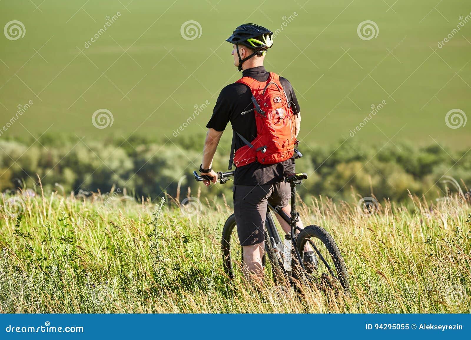 Οπισθοσκόπος του ποδηλάτη που στέκεται με το ποδήλατο βουνών ενάντια στο όμορφο τοπίο