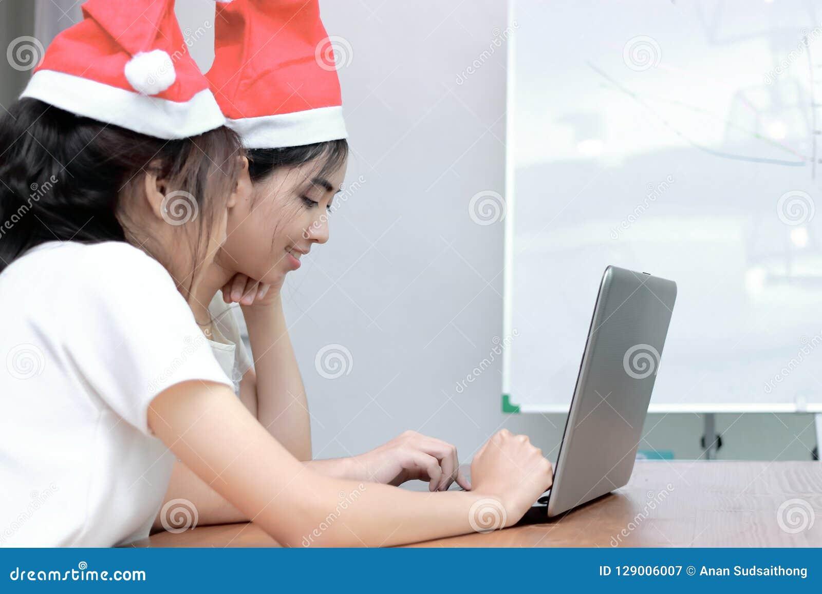 Οπισθοσκόπος των εύθυμων νέων ασιατικών γυναικών στα καπέλα Santa που ψωνίζουν on-line με το lap-top στο καθιστικό στο σπίτι Χαρο