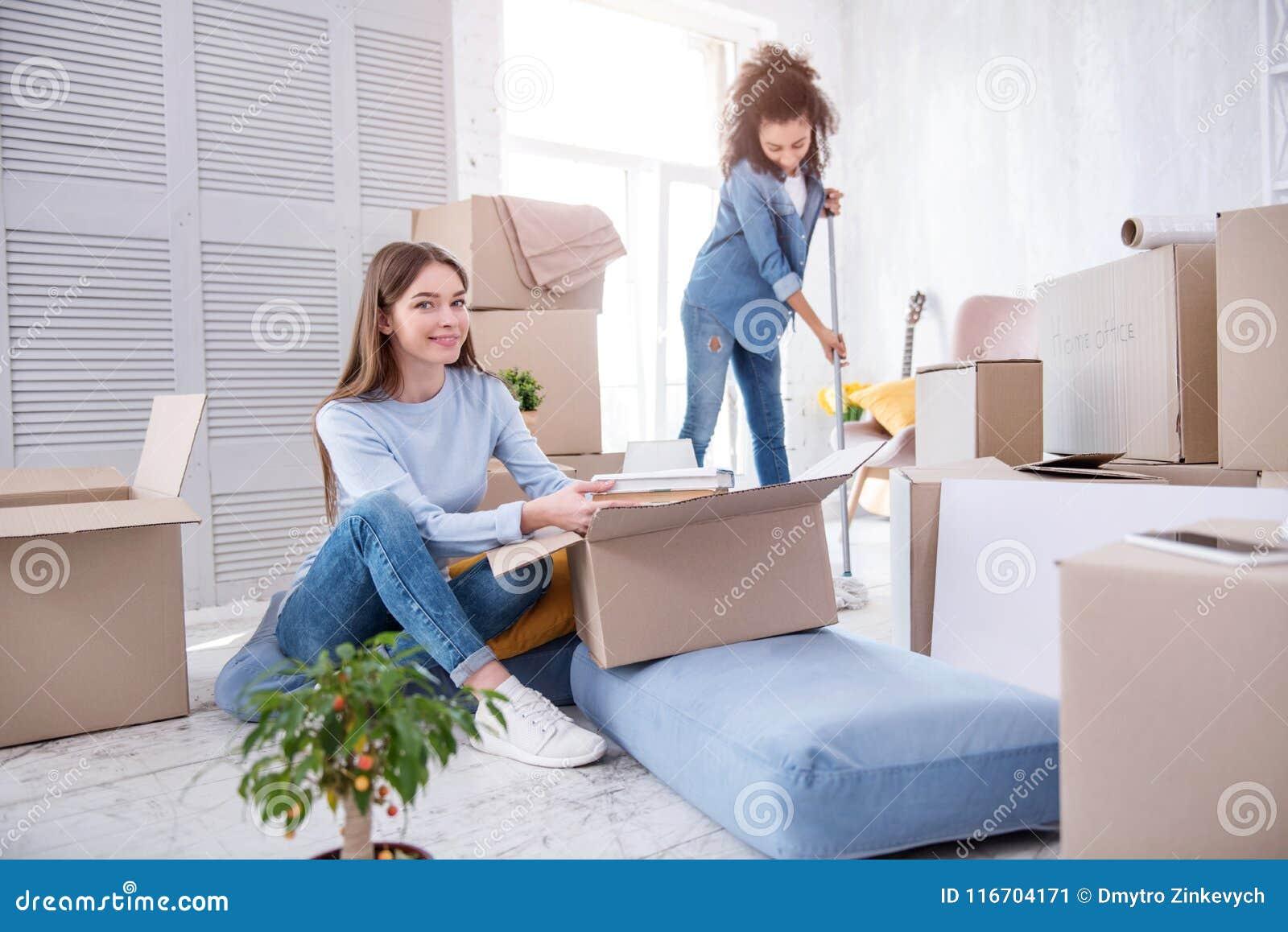 Οπτιμιστείς γυναίκες σπουδαστές που ανοίγουν και που καθαρίζουν dorm το δωμάτιο