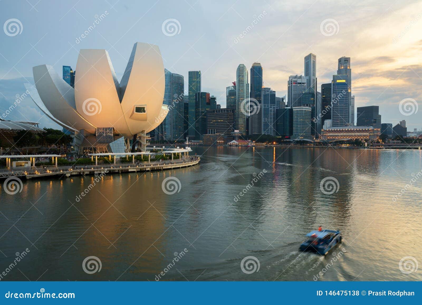 Ορίζοντας εμπορικών κέντρων της Σιγκαπούρης και ουρανοξύστης της Σιγκαπούρης στη νύχτα στον κόλπο μαρινών r