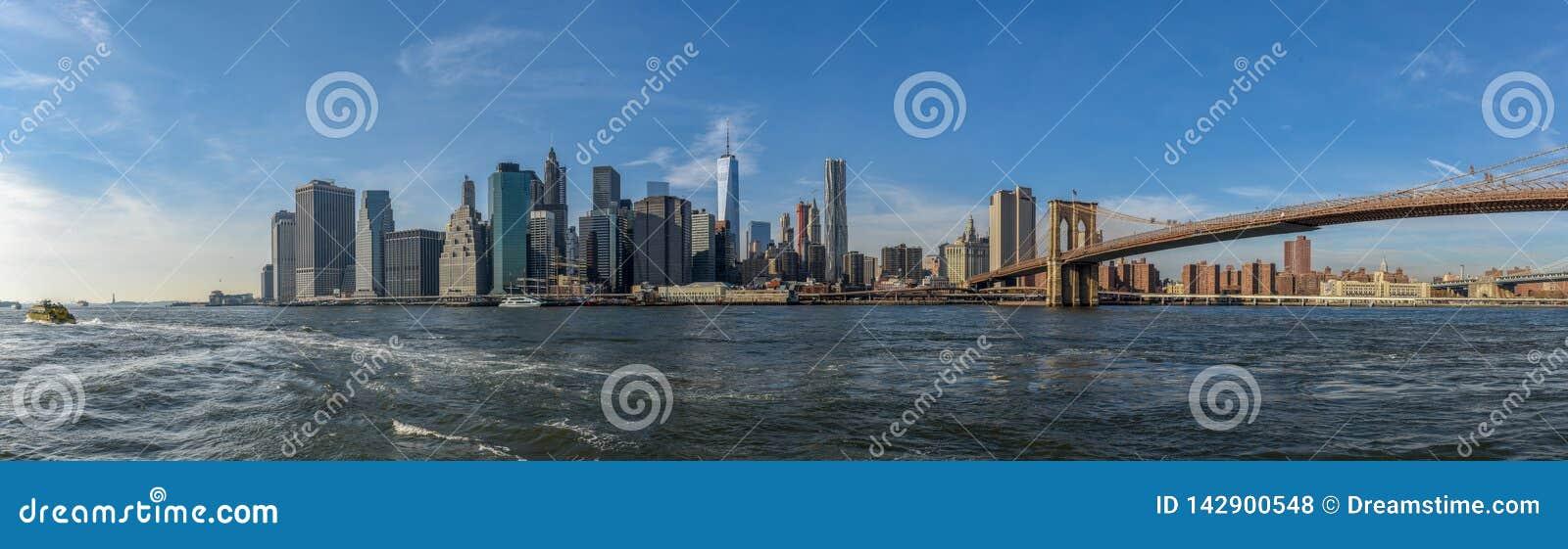 Ορίζοντας του Μανχάταν μια ηλιόλουστη ημέρα με τη γέφυρα του Μπρούκλιν κατά την άποψη