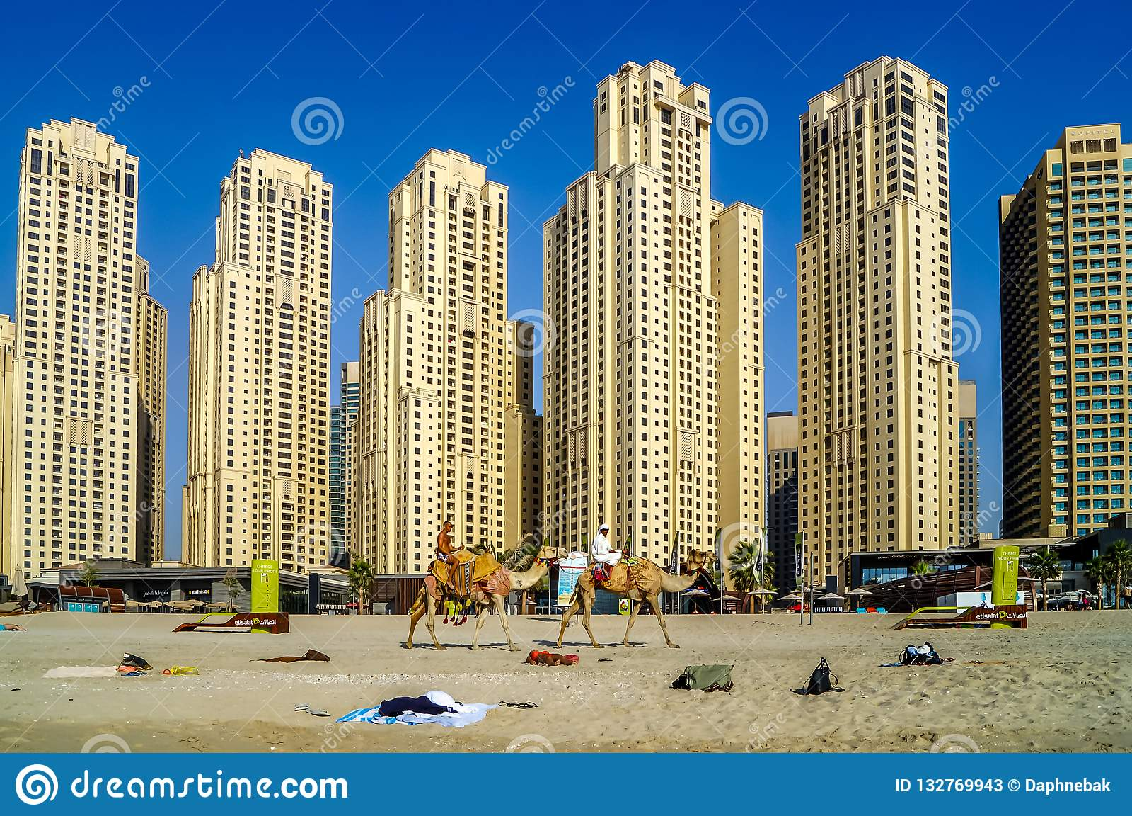 Ορίζοντας του Ντουμπάι με τους ουρανοξύστες και τις καμήλες στην παραλία