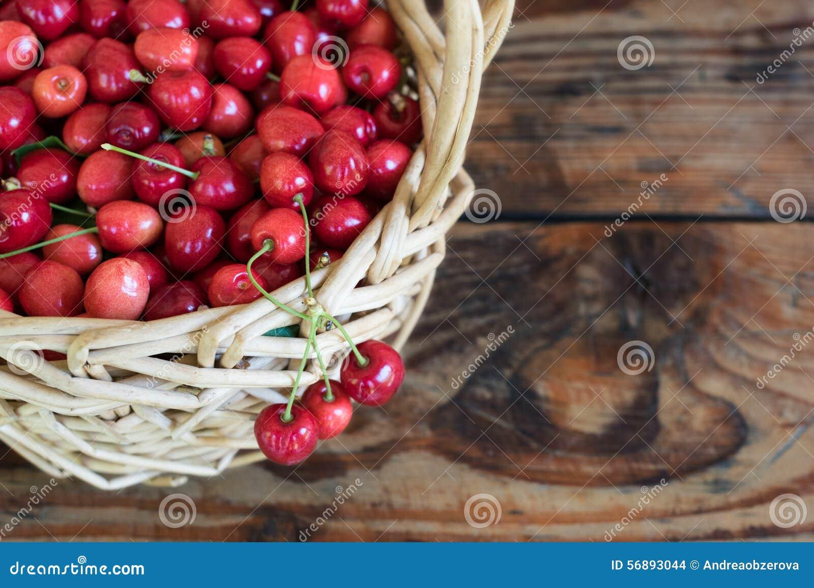 οργανικά homegrown κεράσια σε ένα καλάθι, στο ξύλινο υπόβαθρο