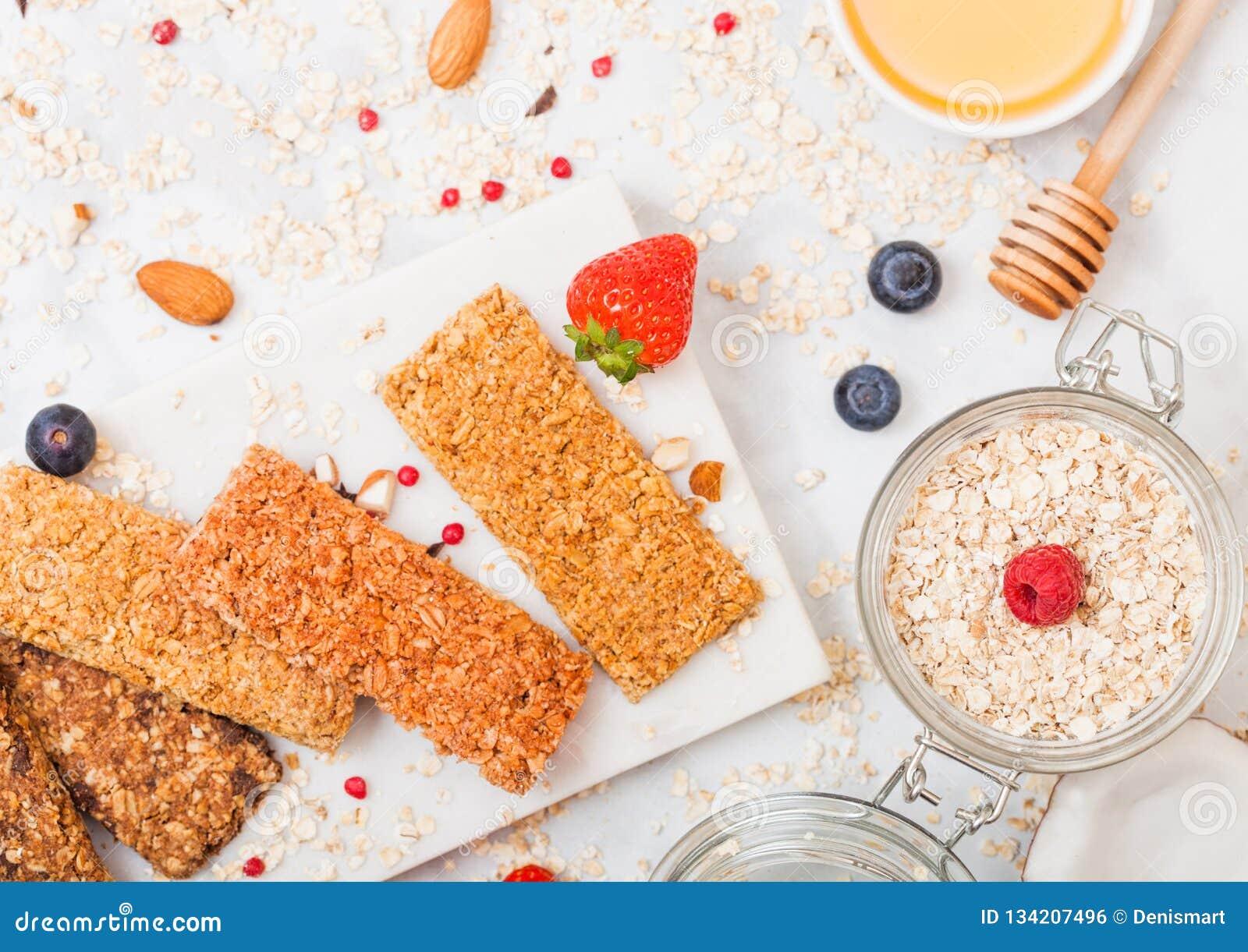 Οργανικός φραγμός granola δημητριακών με τα μούρα στο μαρμάρινο πίνακα με το κουτάλι μελιού και το βάζο των βρωμών και την καρύδα