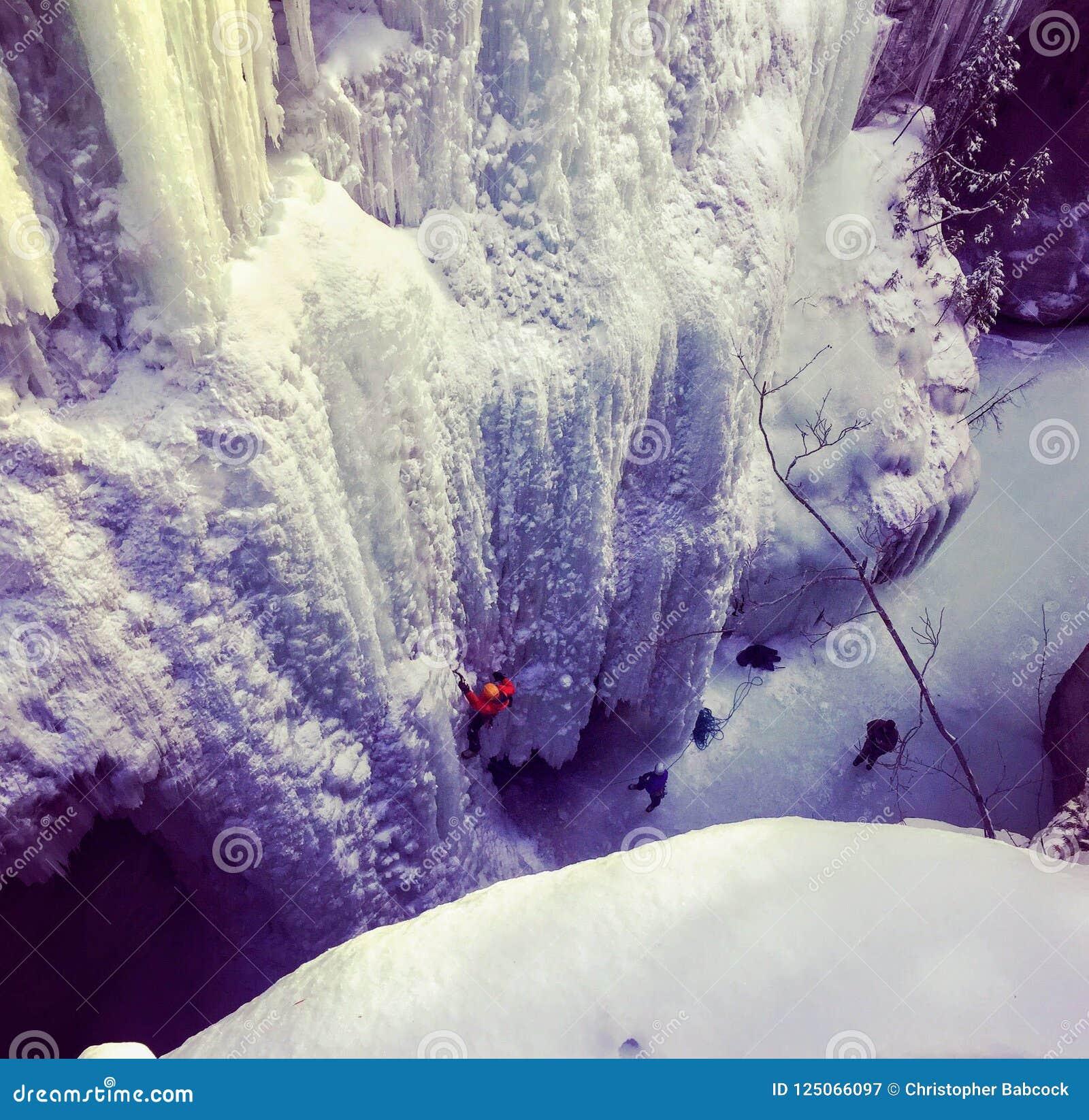 Ορειβάτες πάγου που σκάβουν μέσα με τις επιλογές και τα σκυλιά έλκηθρου πάγου τους ως
