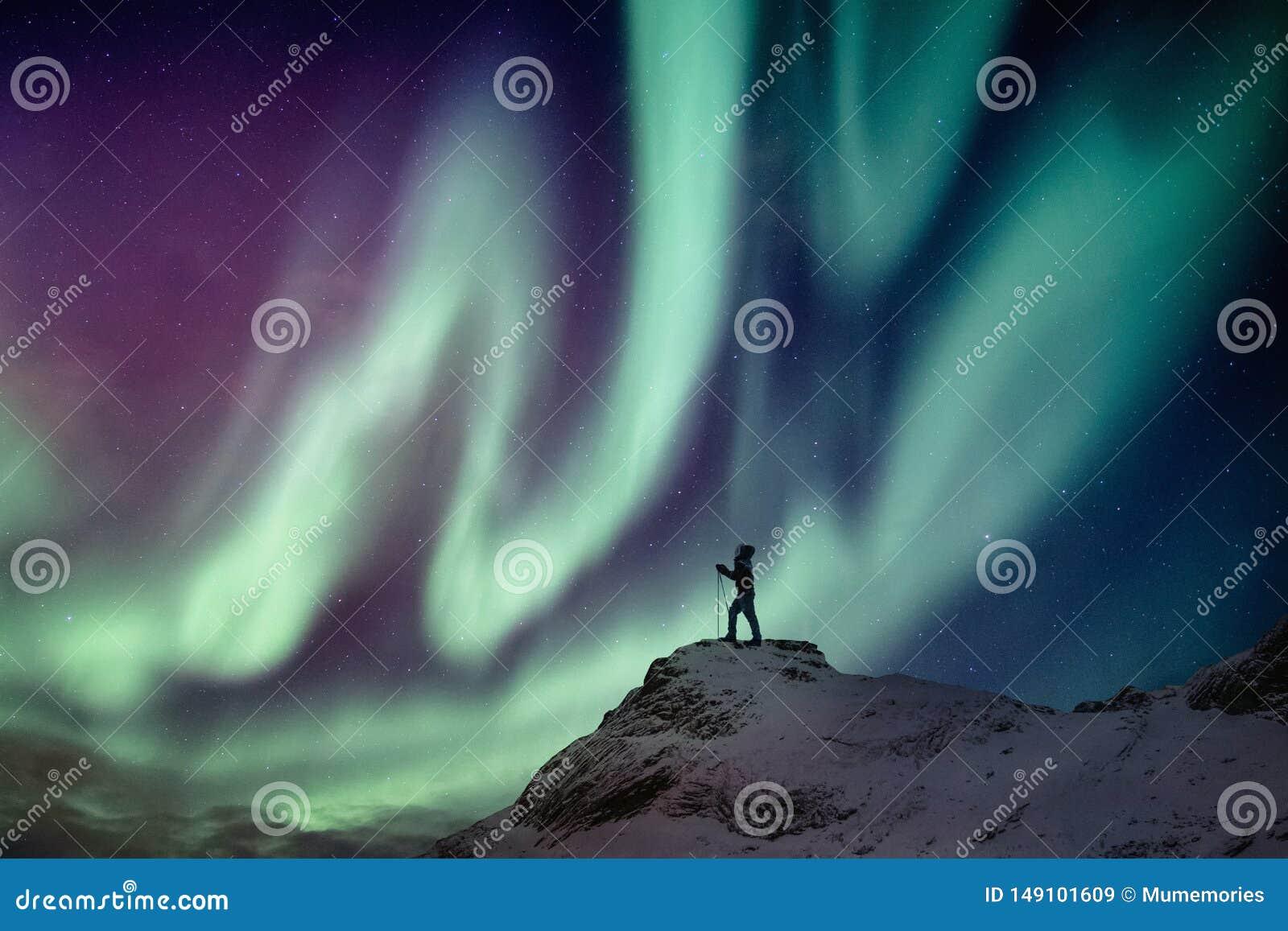 Ορειβάτης ατόμων που στέκεται στη χιονώδη αιχμή με τα borealis αυγής και έναστρος