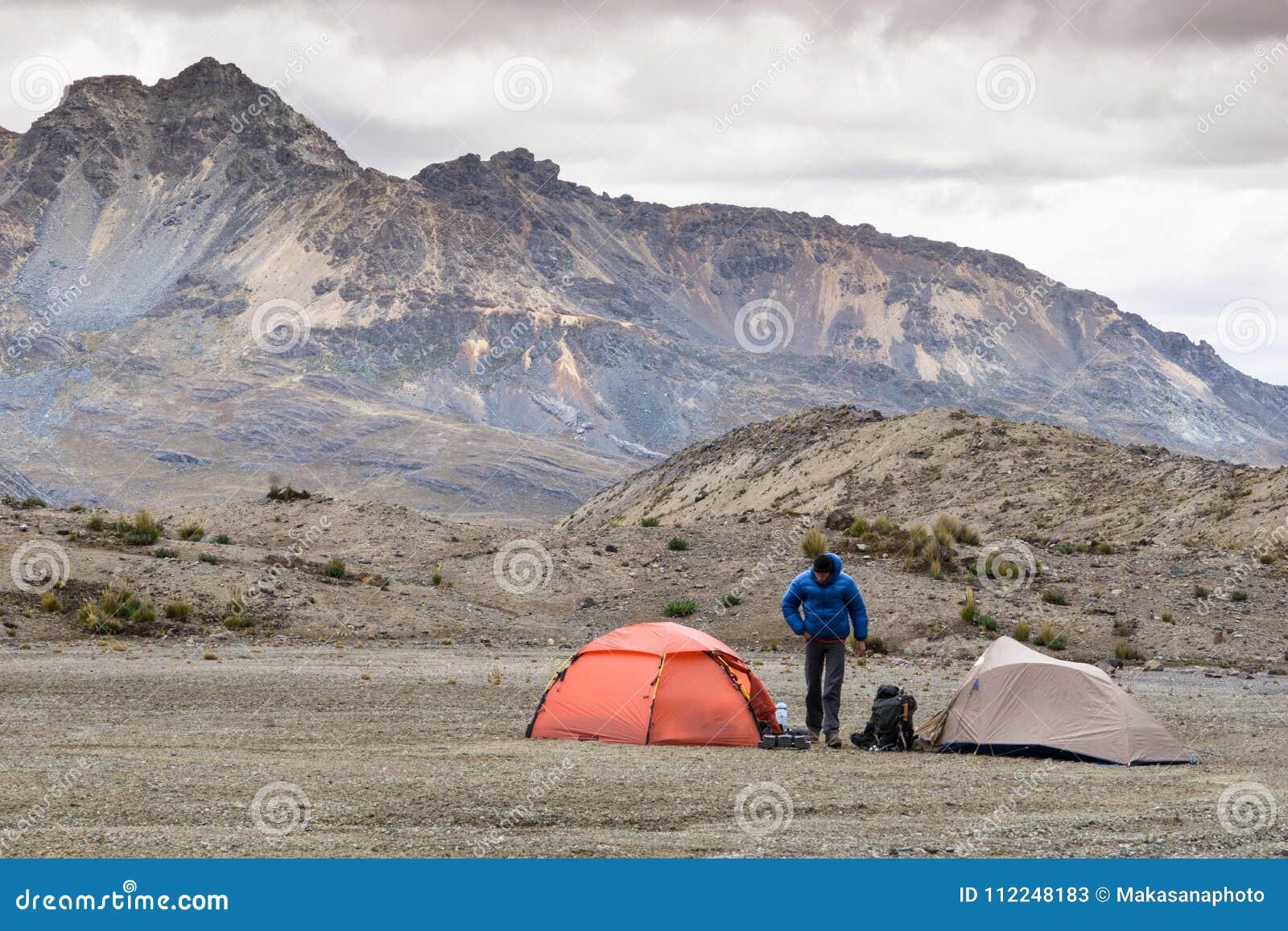 Ορειβάτης βουνών και δύο σκηνές σε μια μακρινή βάση στρατοπεδεύουν στο BLANCA οροσειρών
