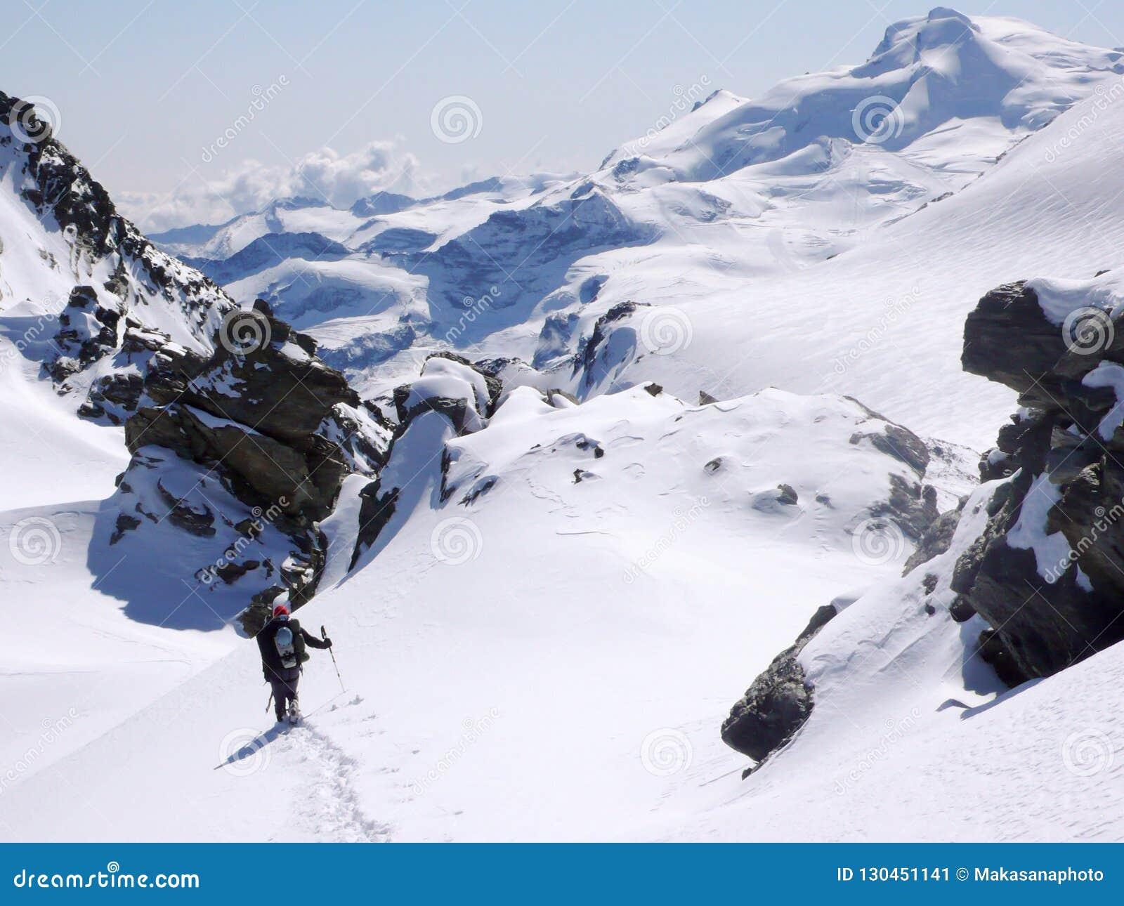 Ορειβάτης βουνών που φέρνει πολύ εξοπλισμό αναρρίχησης στη σειρά βουνών Mischabel στις ελβετικές Άλπεις επάνω από την αμοιβή Saas