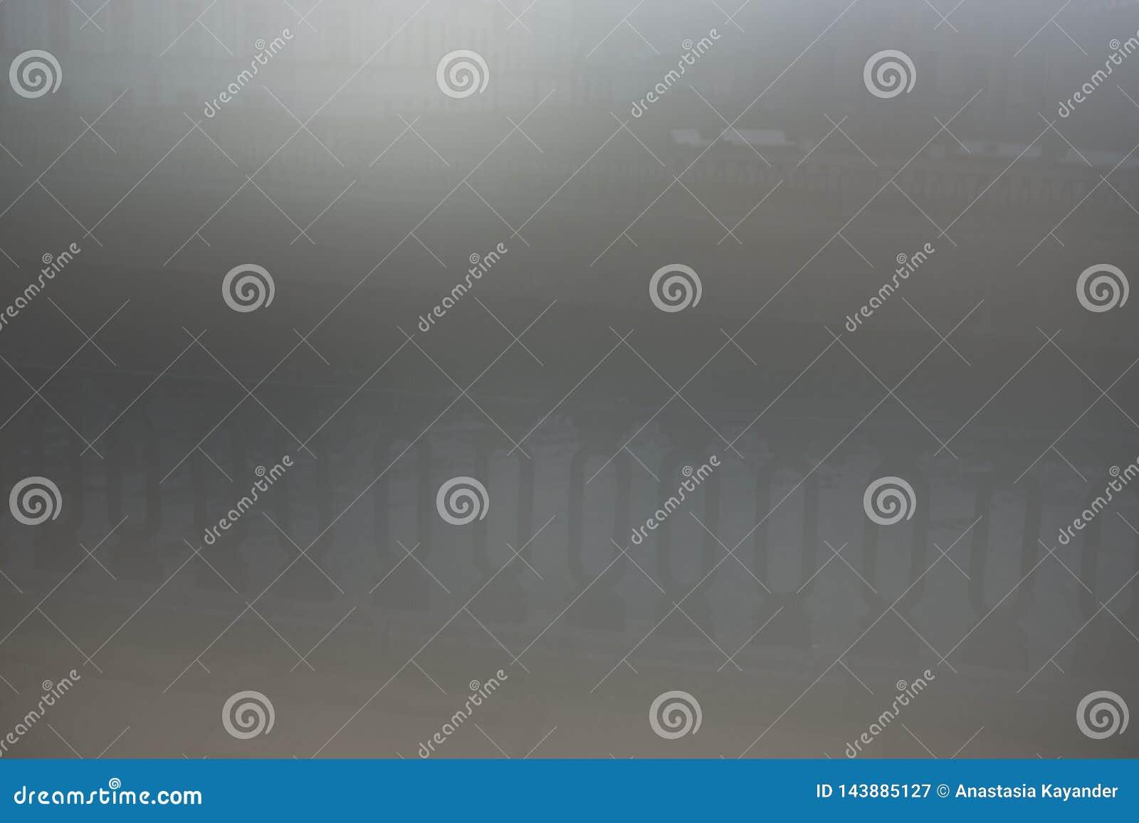 Οριζόντιος φράκτης πόλεων metall στην γκρίζα ομίχλη
