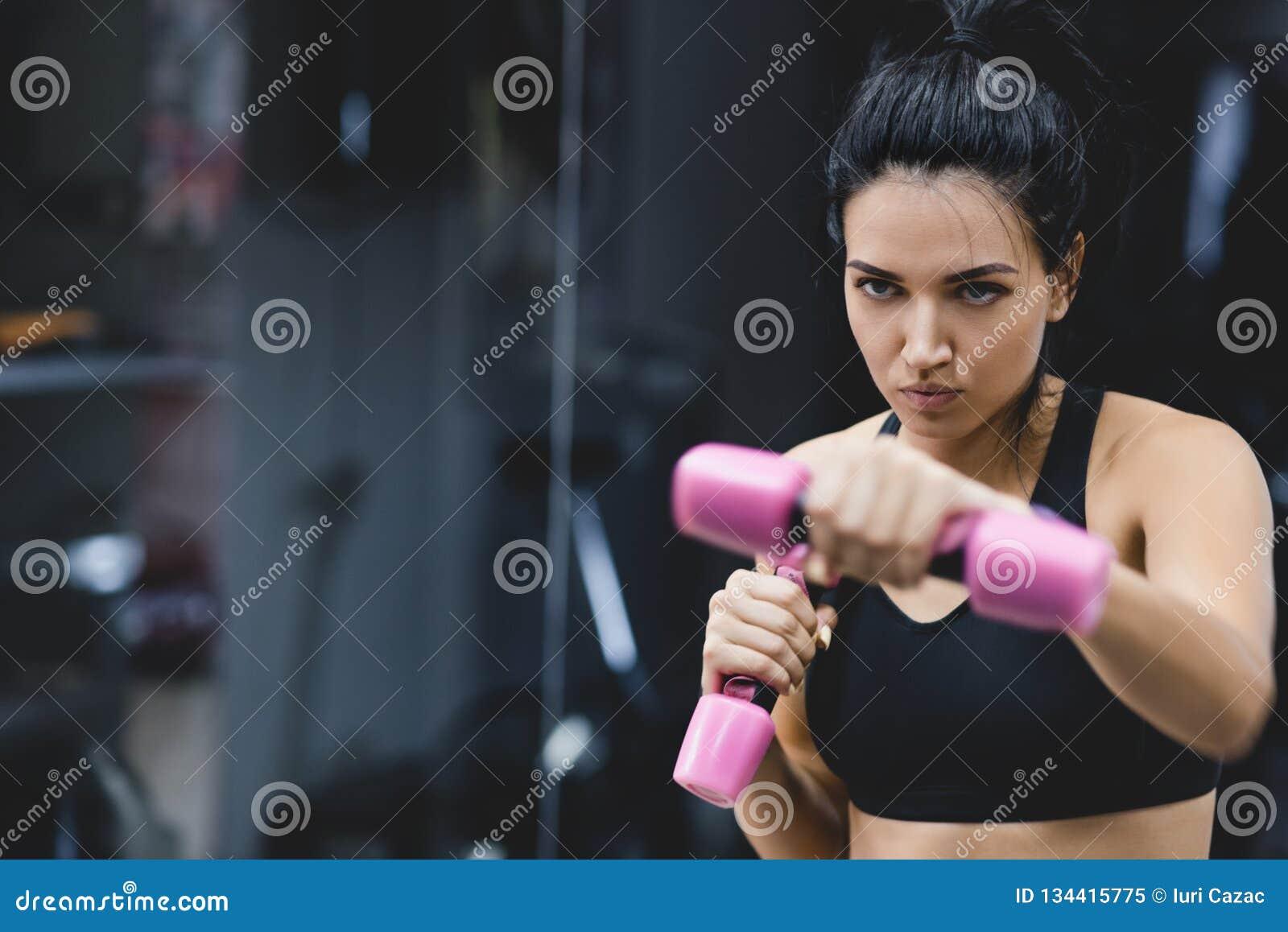 Οριζόντιο πορτρέτο της ισχυρής νέας γυναίκας που κάνει την άσκηση με τους αλτήρες Ευρωπαϊκό θηλυκό ικανότητας που κάνει την έντον