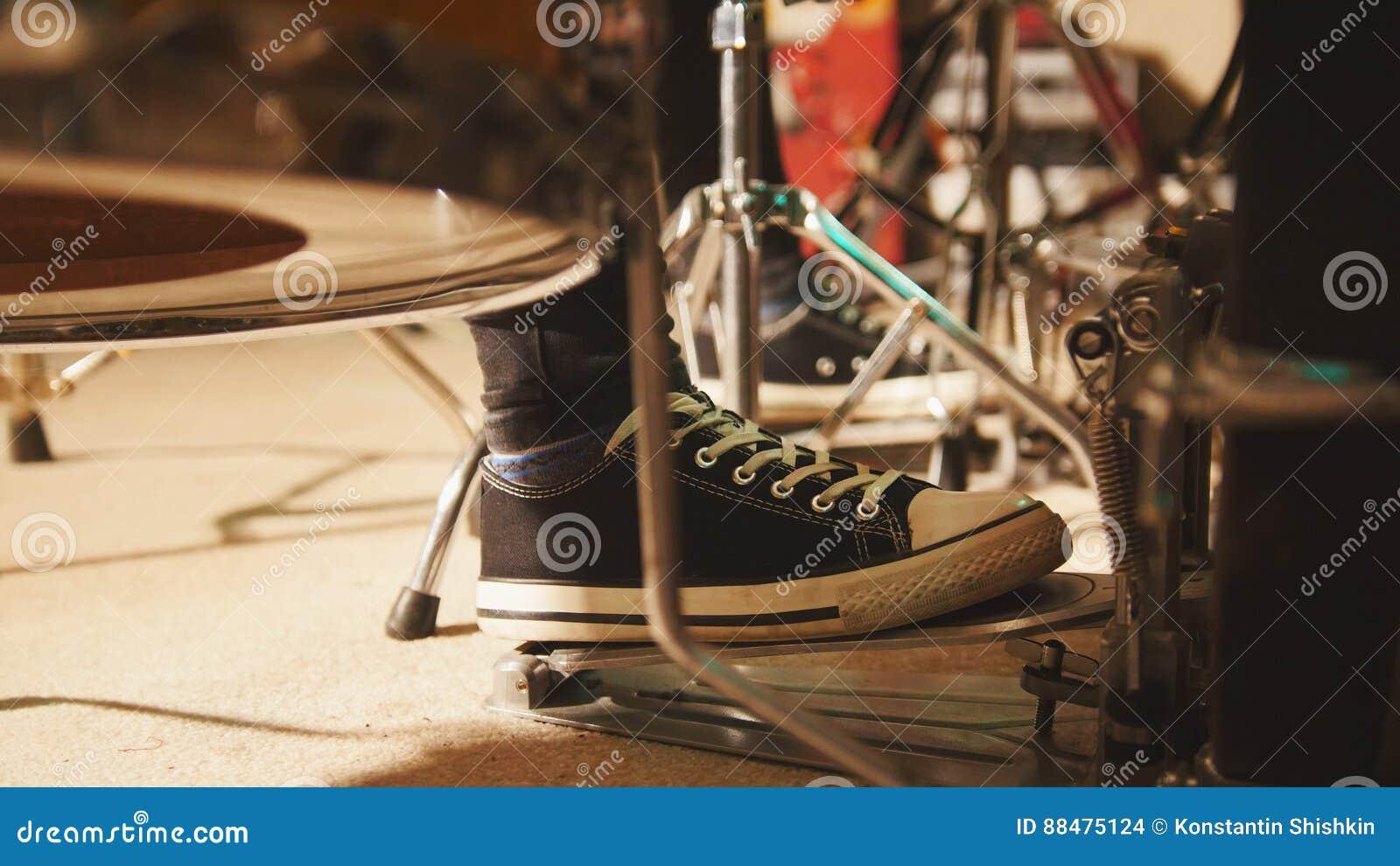 Ορχήστρα ροκ που προετοιμάζει στο γκαράζ - το πόδι τυμπανιστών ` s φορά τα πάνινα παπούτσια που κινούν το βαθύ πεντάλι τυμπάνων