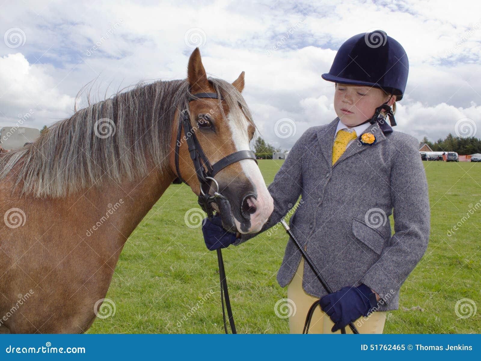 Ουαλλέζικο κορίτσι στη δοκιμή εκπαίδευσης αλόγου σε περιστροφές στο σκληρό καπέλο με το πόνι