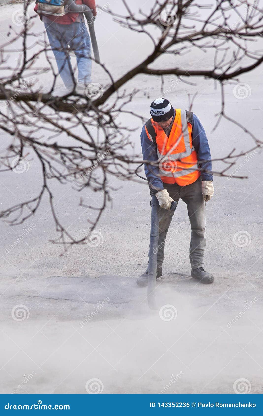 Ουκρανία, Shostka, οδός της Mira - 26 Μαρτίου 2019: Οι εργαζόμενοι επισκευάζουν το δρόμο ασφάλτου