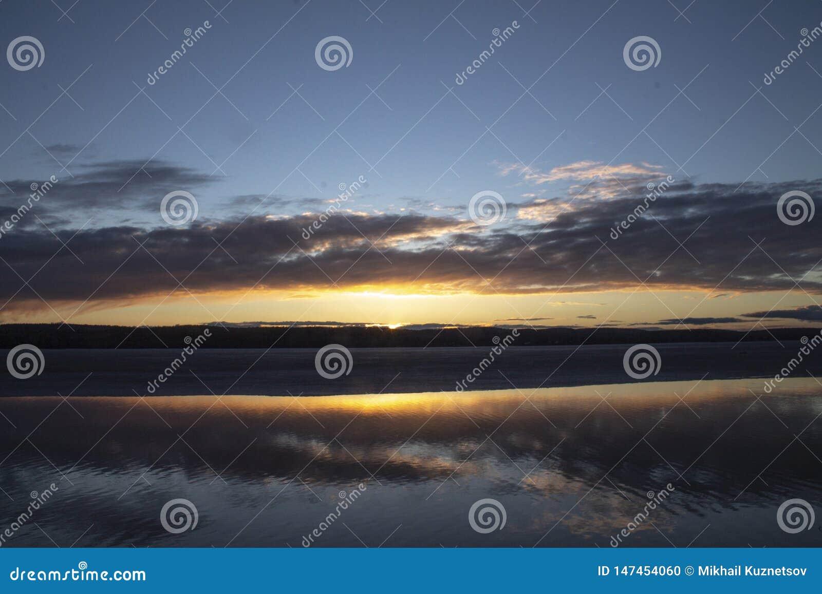 Ουρανός ηλιοβασιλέματος στη λίμνη με τα σύννεφα